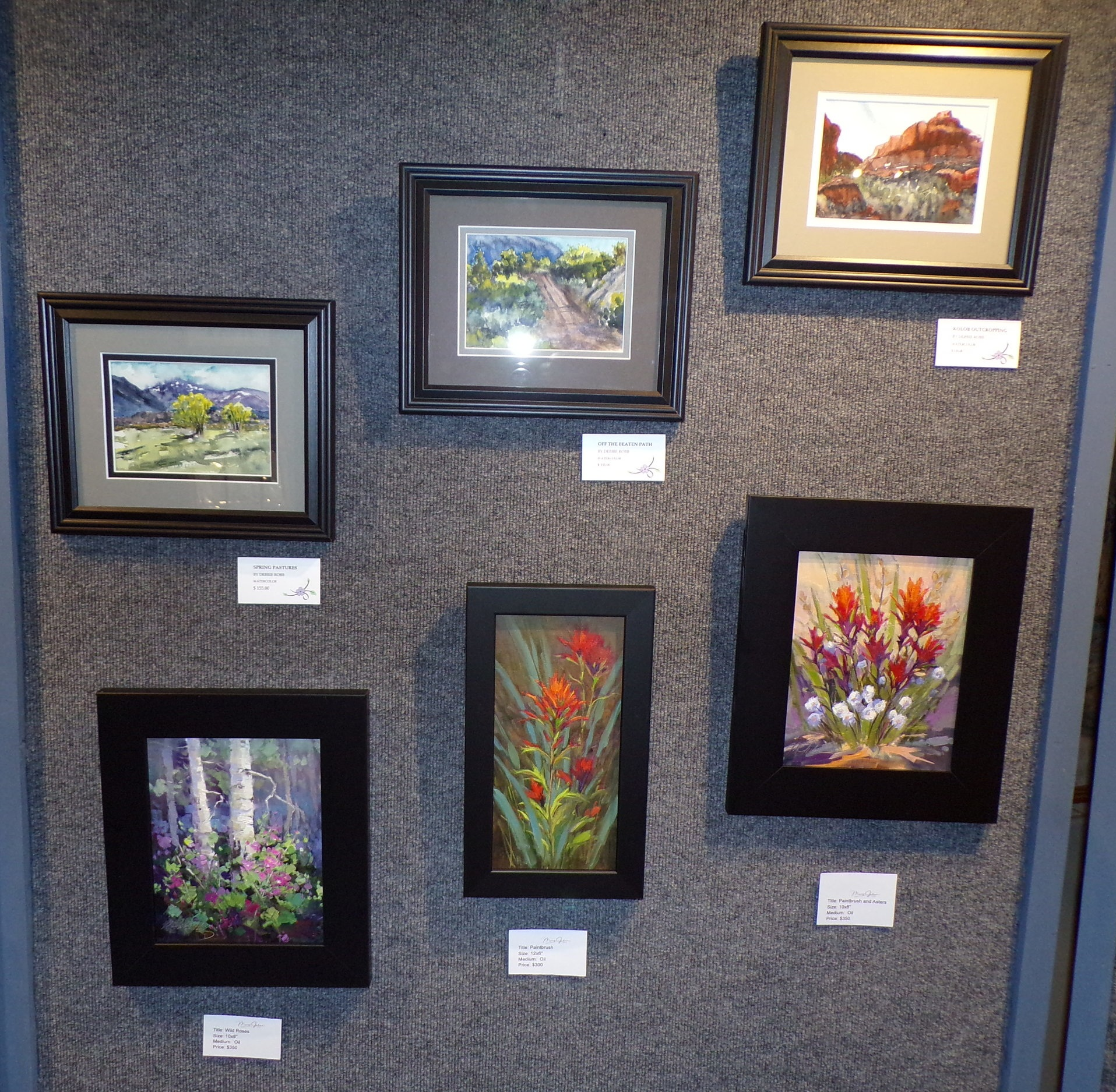 Three watercolors by Debbie Robb and three oil paintings by Mary Jabens.
