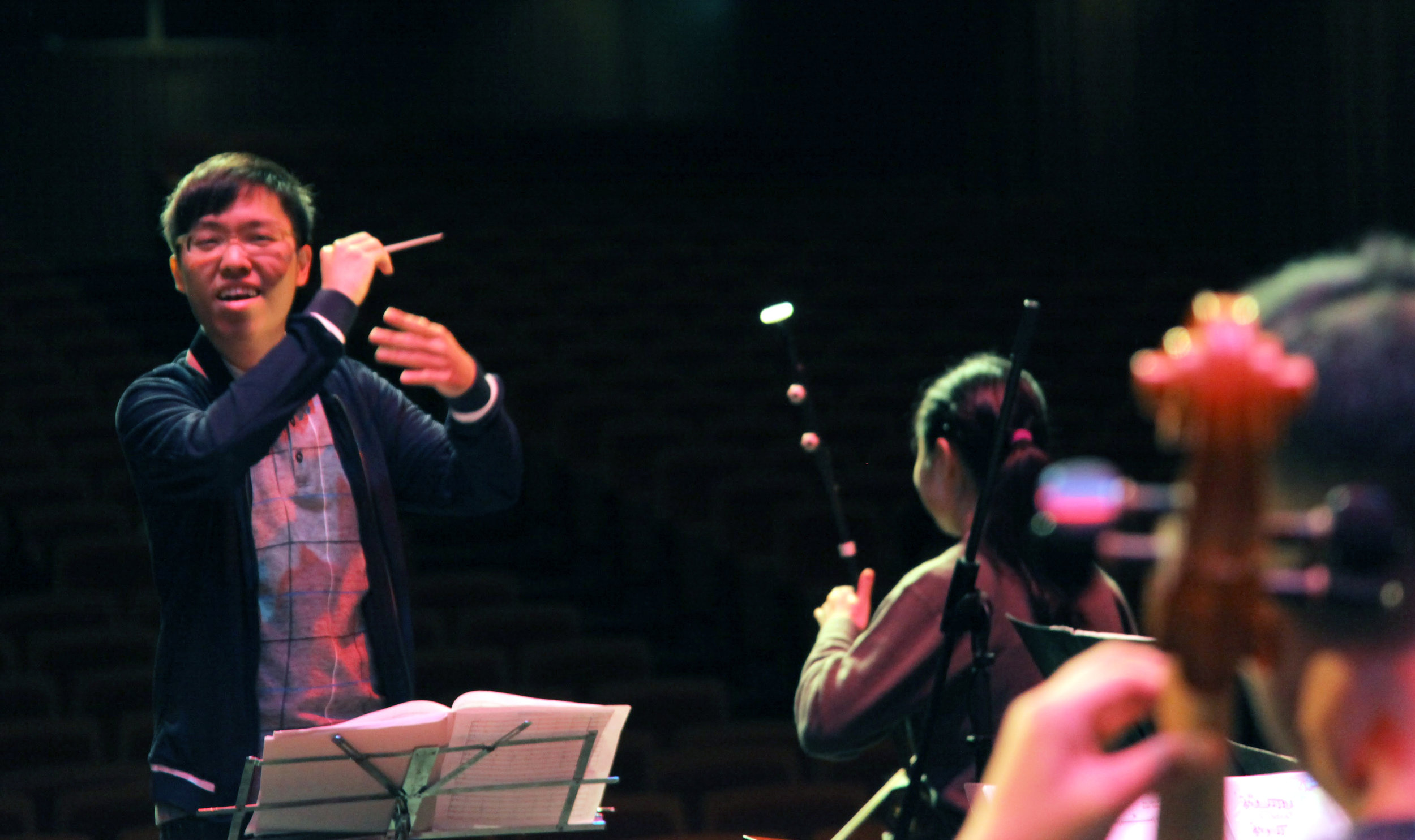 Above: Sulwyn Lok (left) leads his orchestra through a rehearsal.