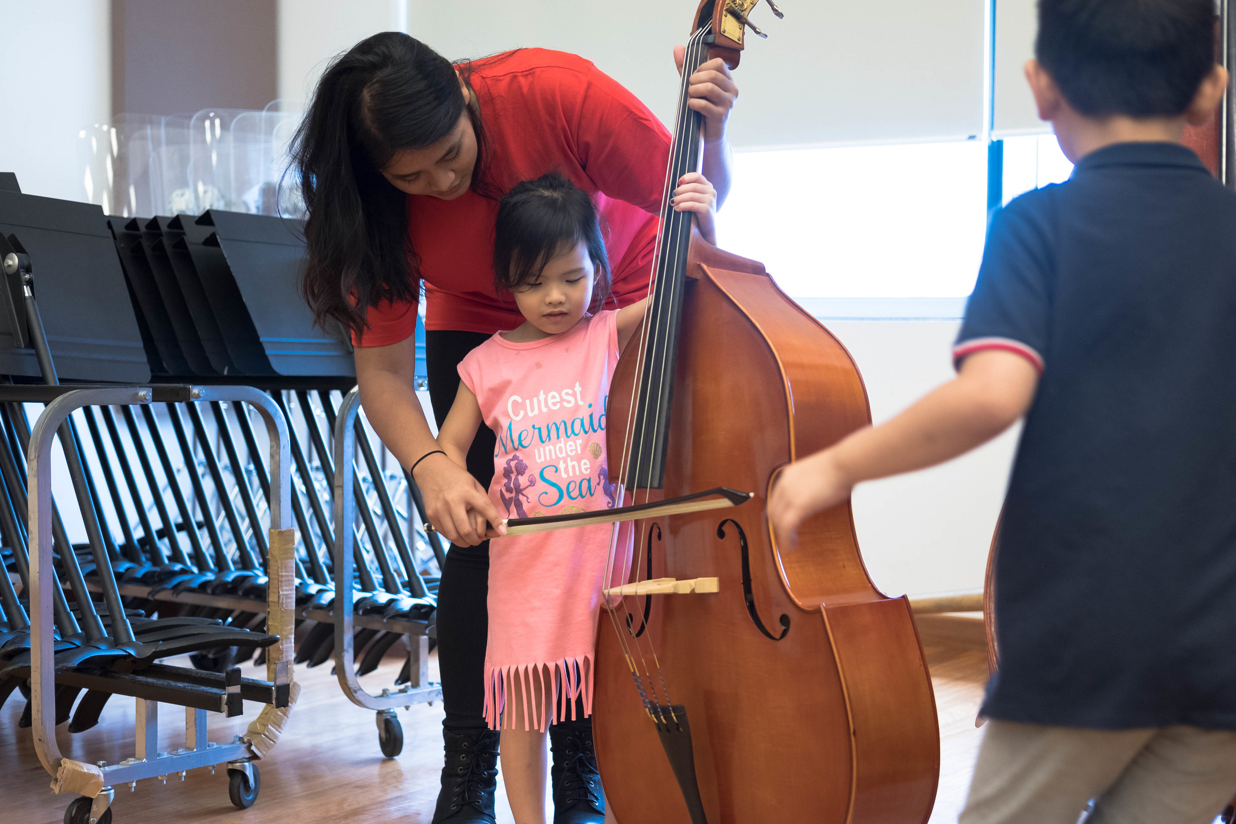 Year 3 student Dahlia Neniel introducing the double bass to a young participant