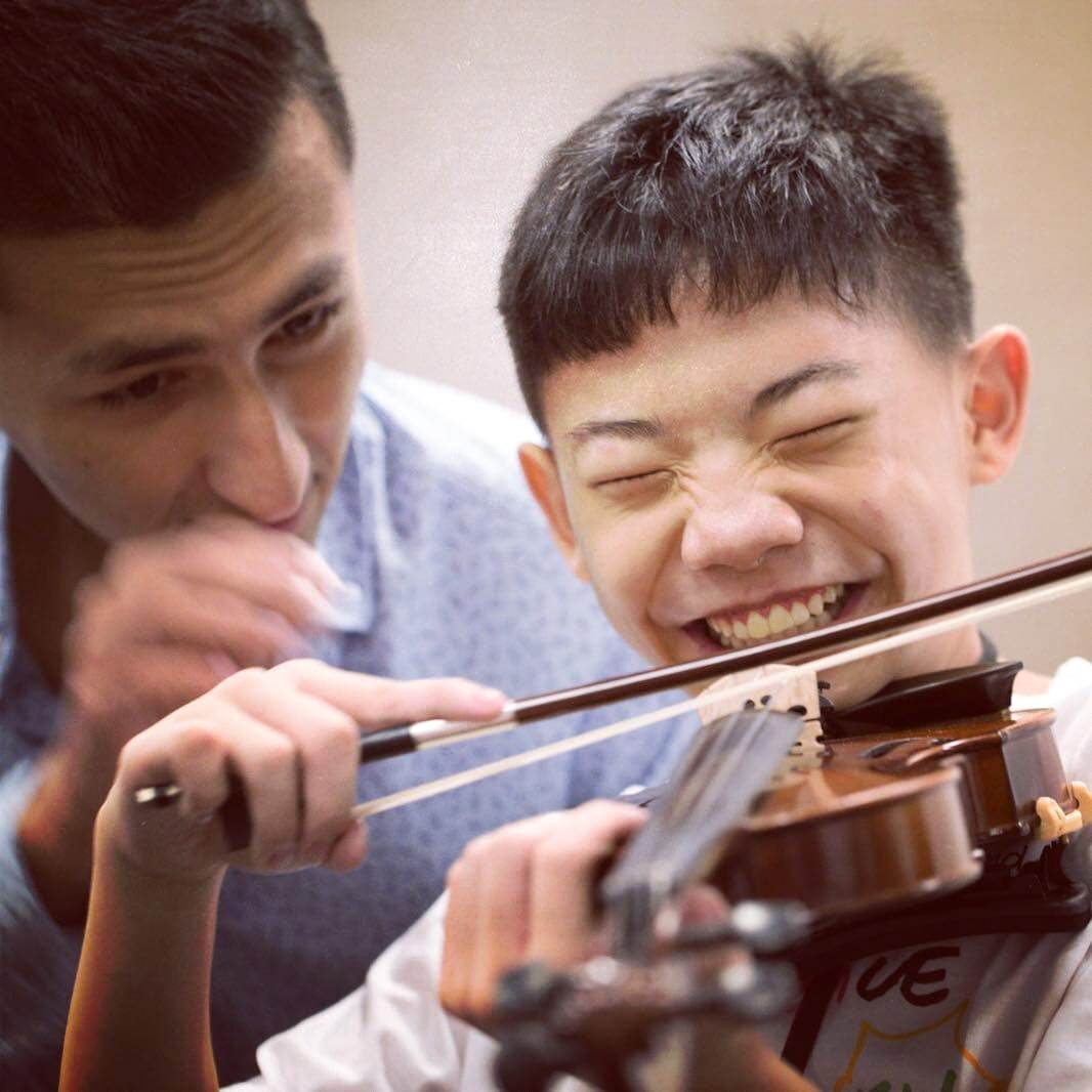 Dior guiding a young student at the Singapore International String Conference