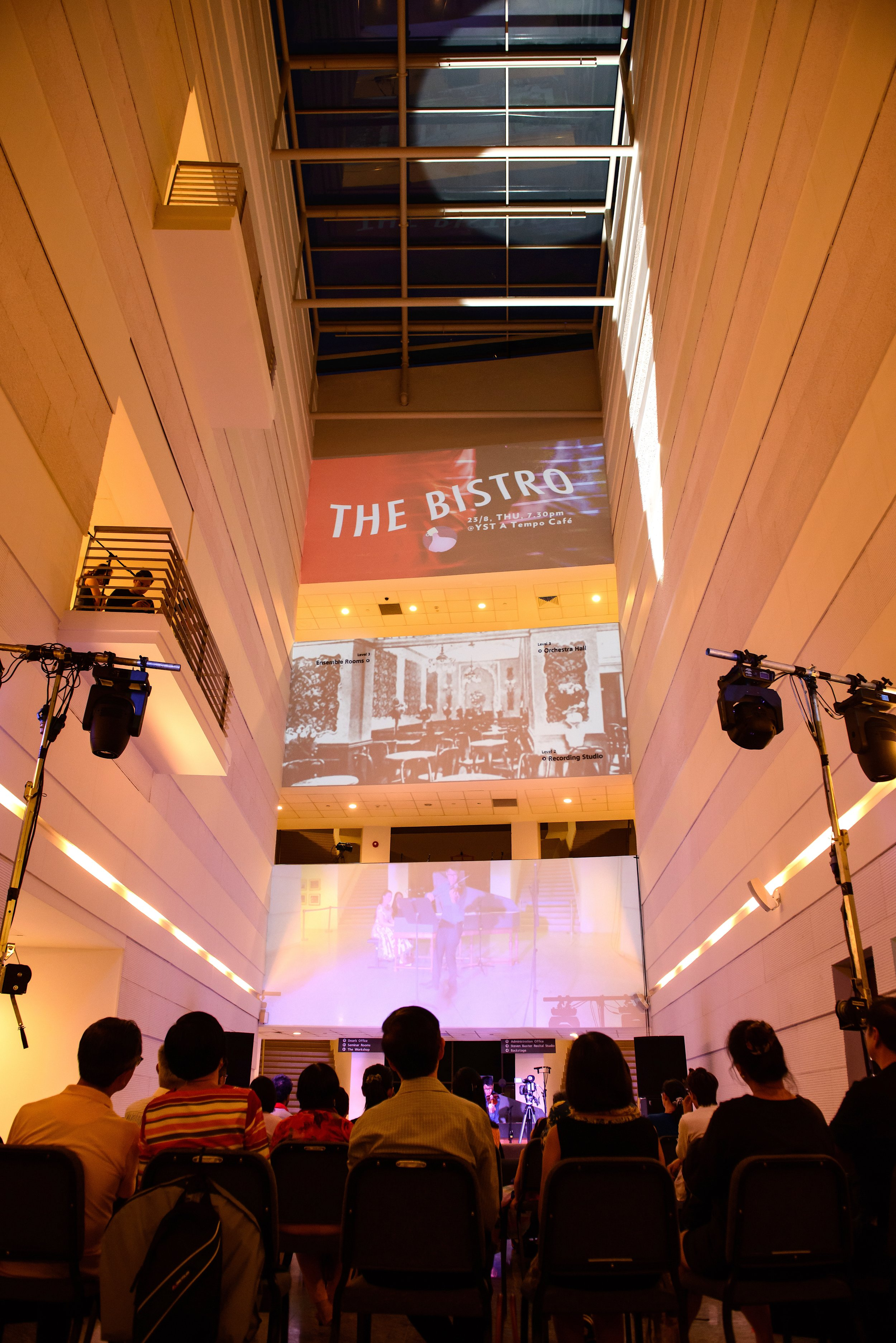 The third concert,  The Bistro , took place in the open space of the YST ground level walkway, with light projections on the central white walls of the YST building.