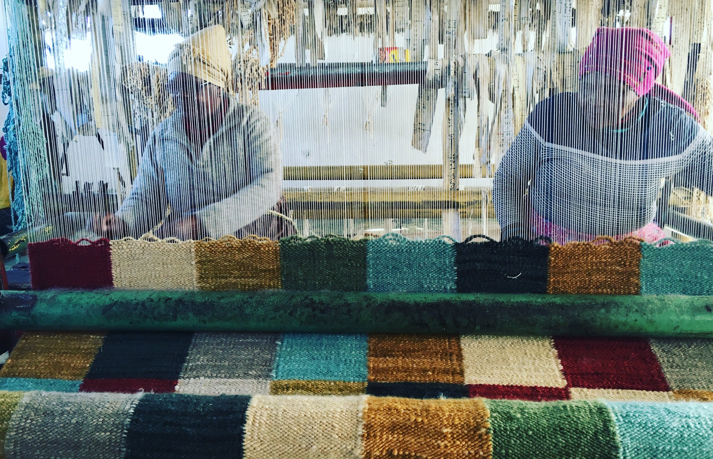 TWO WOMEN WEAVE TOGETHER ON A HAND MADE LOOM, SKILFULLY FOLLOWING PATTERNS AS THEY PLAIT THE YARN THROUGH THE WEFT.