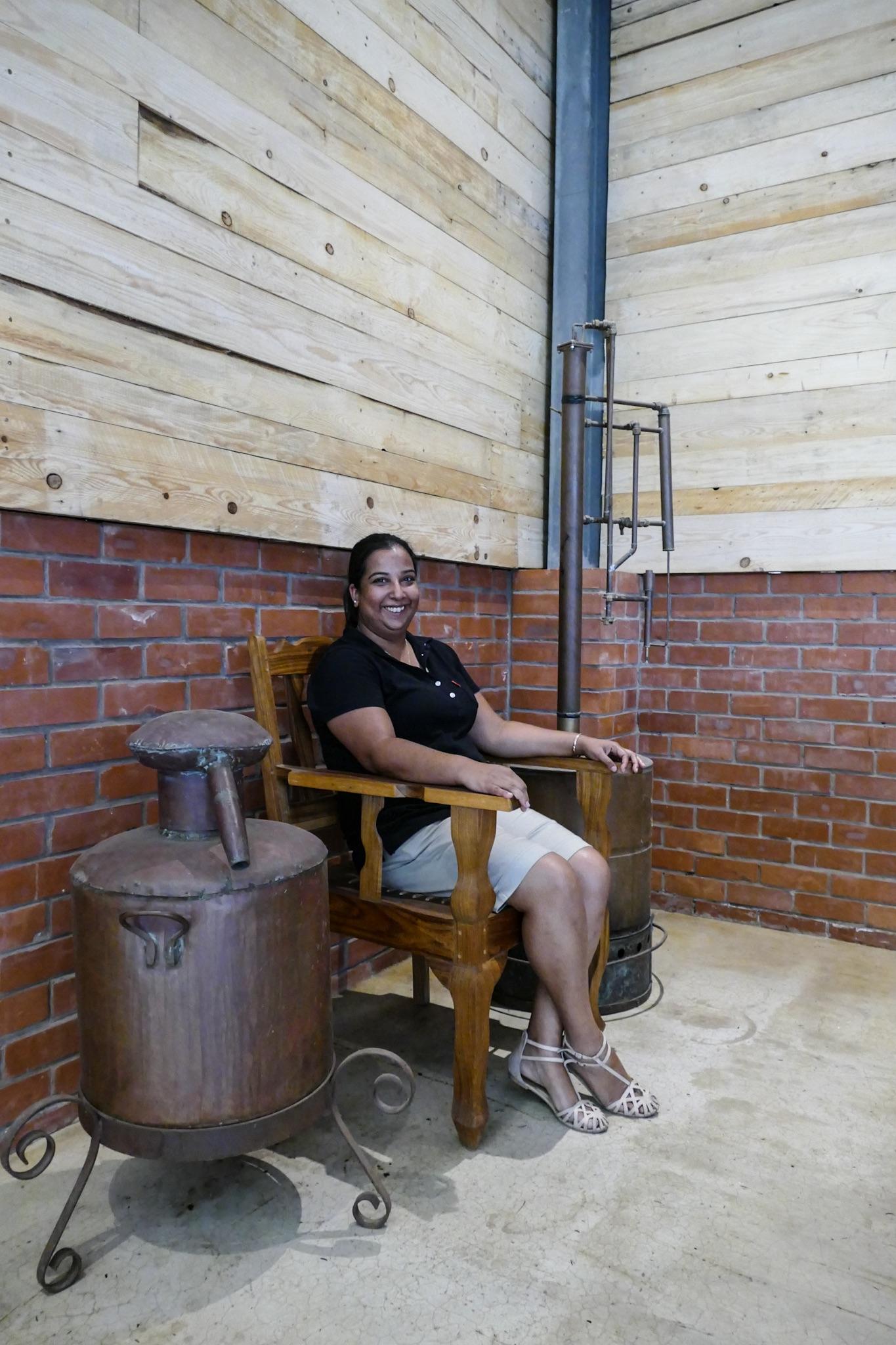 Melissa Peter, the distiller at Tapanga Rum sitting between the original Tapanga Rum stills.