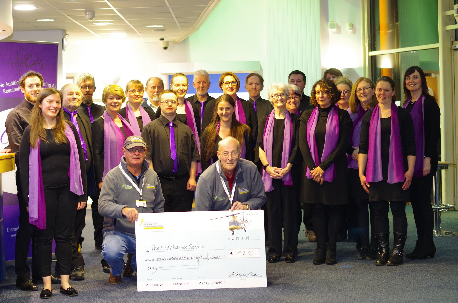 Melody Choir handing over their cheque with funds raised for Air Ambulance
