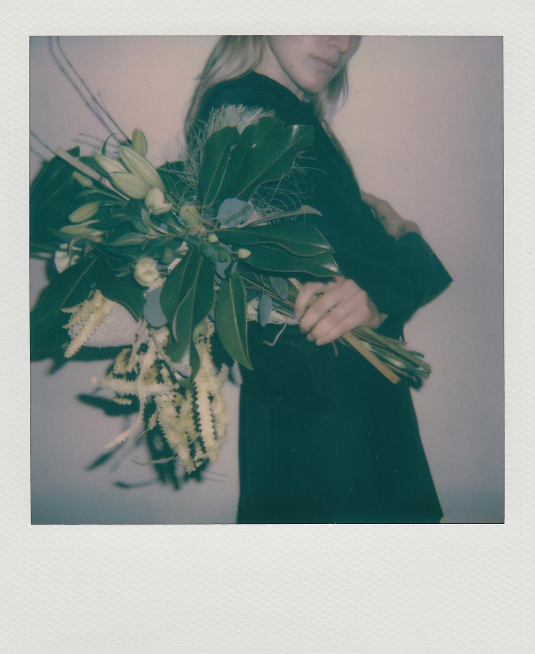 """blazé bouquet - BLAZÉ MILANO è lieta di annunciare il lancio di una collaborazione esclusiva con la flower designer Irene Cuzzaniti. In linea con lo spirito femminile del marchio, Irene ha creato tre diverse composizioni, in tre dimensioni e che portano il nome di tre collezioni di Blazé Milano: Queen of Hearts, Theatre of Dreams e The Essentials. I bouquet combinano un look romantico e delicato con un tocco grafico, che richiama le influenze maschili radicate nelle creazioni di Blazé Milano.In particolare, Irene ha selezionato dei fiori stagionali dalle dimensioni importanti, che includono protee esotiche, allium, orchidee e amaranto, per un tocco teatrale. La palette di colore è giocata su tonalità di arancione, verde e viola, con tocchi di blu.Per presentare questo progetto speciale, Blazé Milano ha chiesto al fashion designer e artista Christian Boaro, che l'anno scorso ha svelato la mostra fotografica """"The Naked Truth,"""" di scattare una serie di suggestive Polaroids dove i bouquet di Irene sono immortalati con giacche iconiche del brand."""