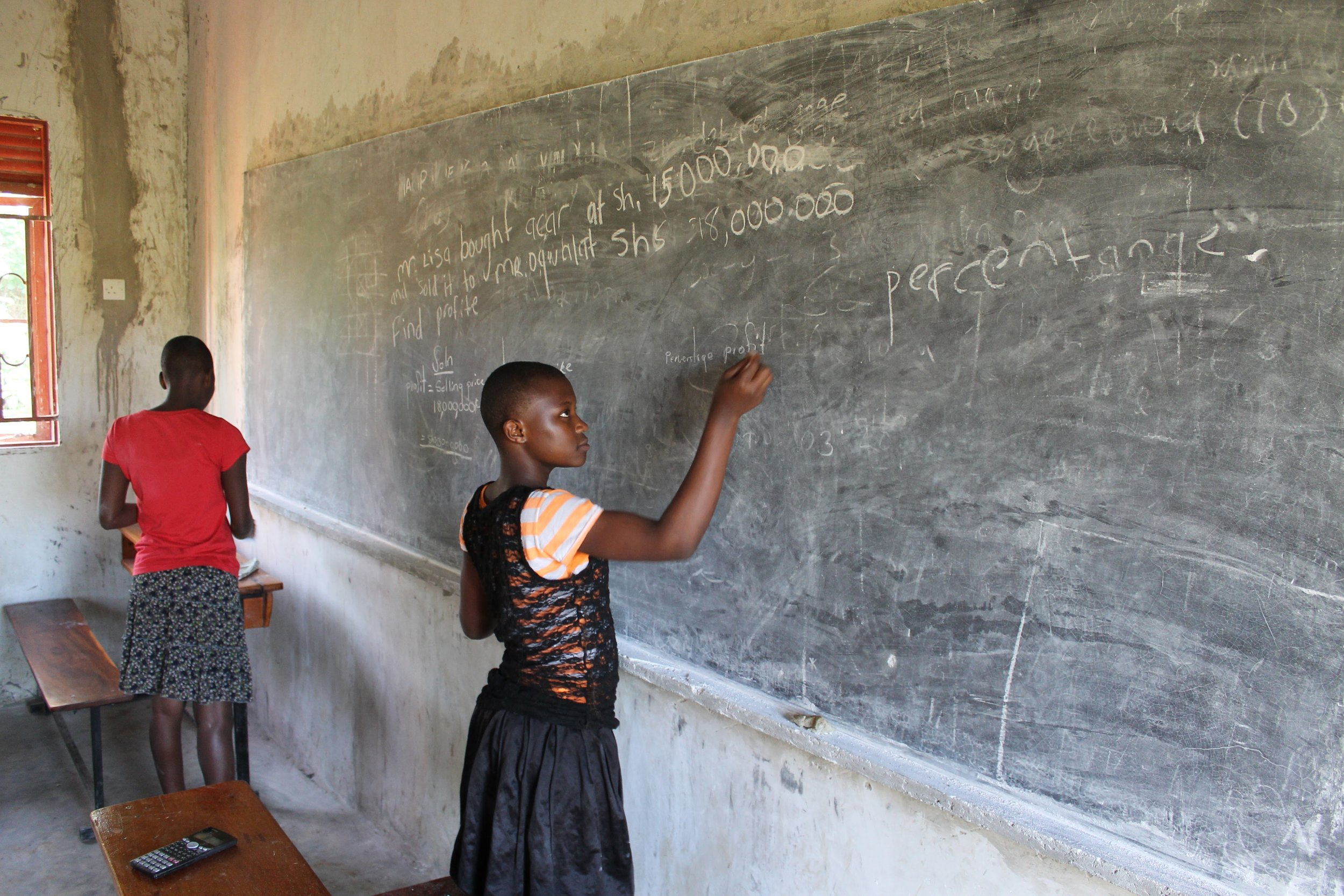 Female Middle School Students at Bulamu working after class on math problems.