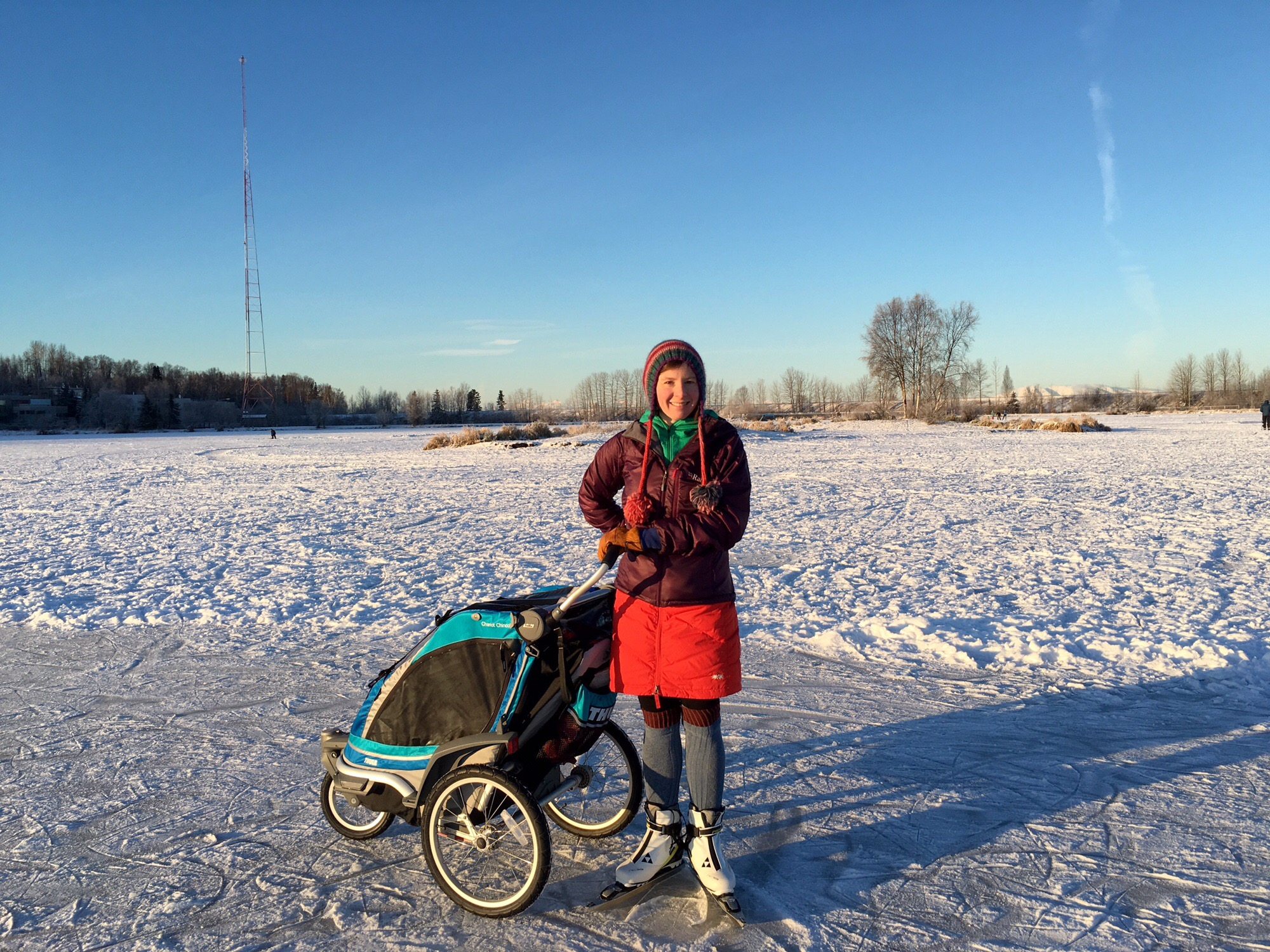 Out on the ice, skating, stroller in hand.