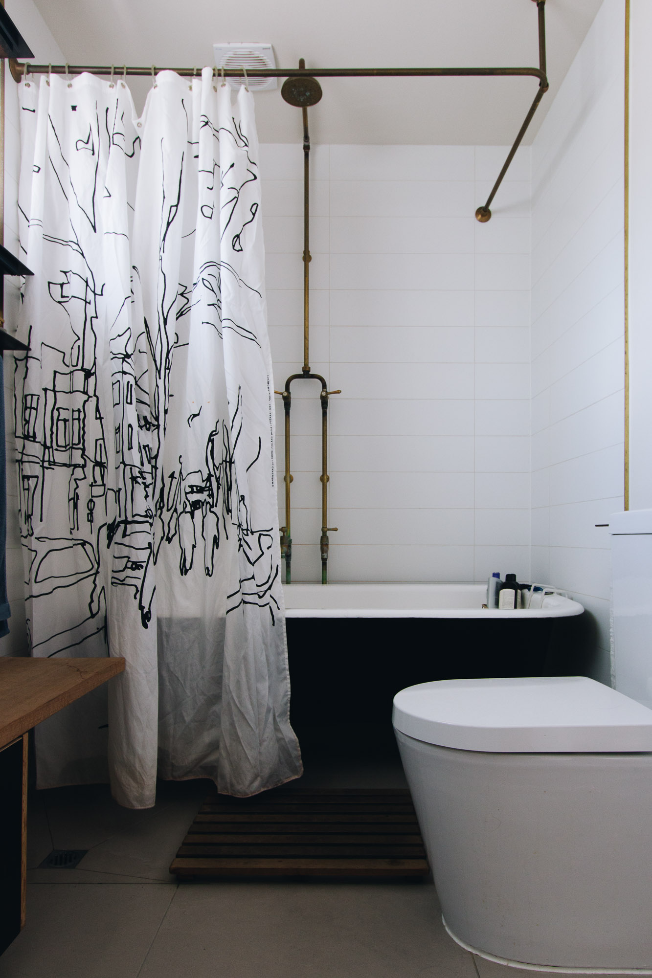 The bathroom reflects other spaces in the house where old meets new and recycled meets sustainable technology. The bath was bought second hand and painted by Joan before we installed it. The brass tap ware reflects all the door furniture and taps throughout the house made of raw brass. Jeremy has used timber and form ply in here too and we have installed a  Marimekko  shower curtain in the black and white colour scheme. The floor is covered by large soft grey Italian tiles from  Signorino  in Richmond. The wall tiles are a simple long white tile used in the bathrooms and kitchen. The toilets are very low water use and are refilled from tank water.