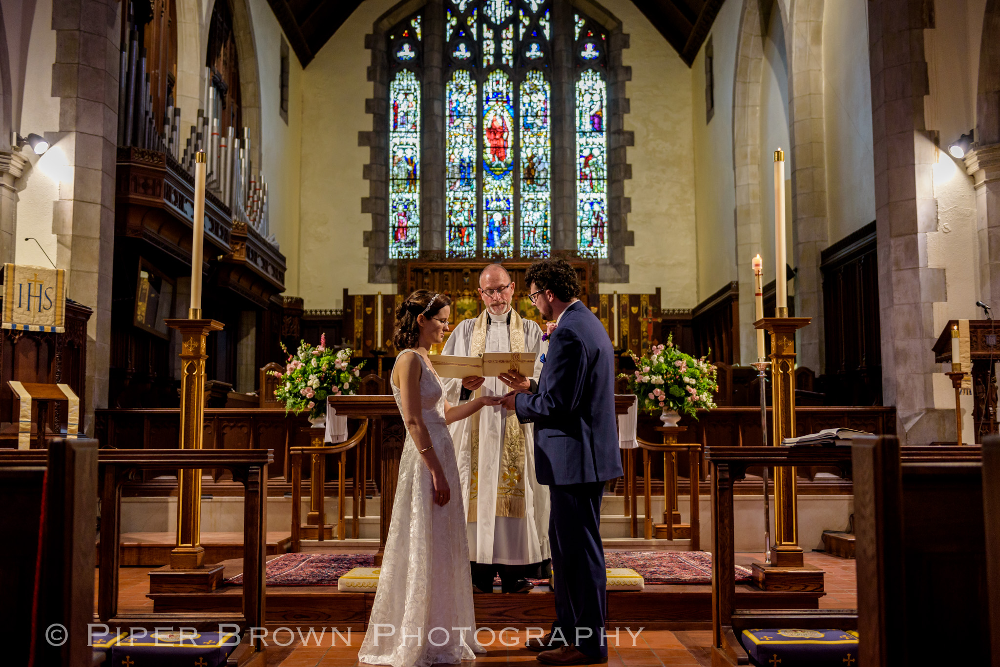 Slim brunette bride in a white embroidered gown exchanging rings with a Curley haired brunette groom in a navy suit in front of a priest in a church with ornate stain-glass window behind them.