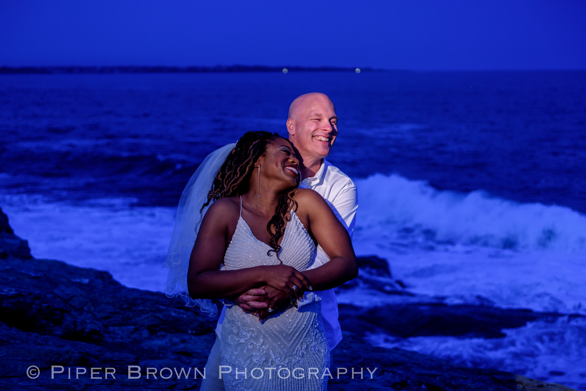 Black smiling woman in a beaded shoe-string wedding dress embraced by laughing white bald man with mean surf behind them.