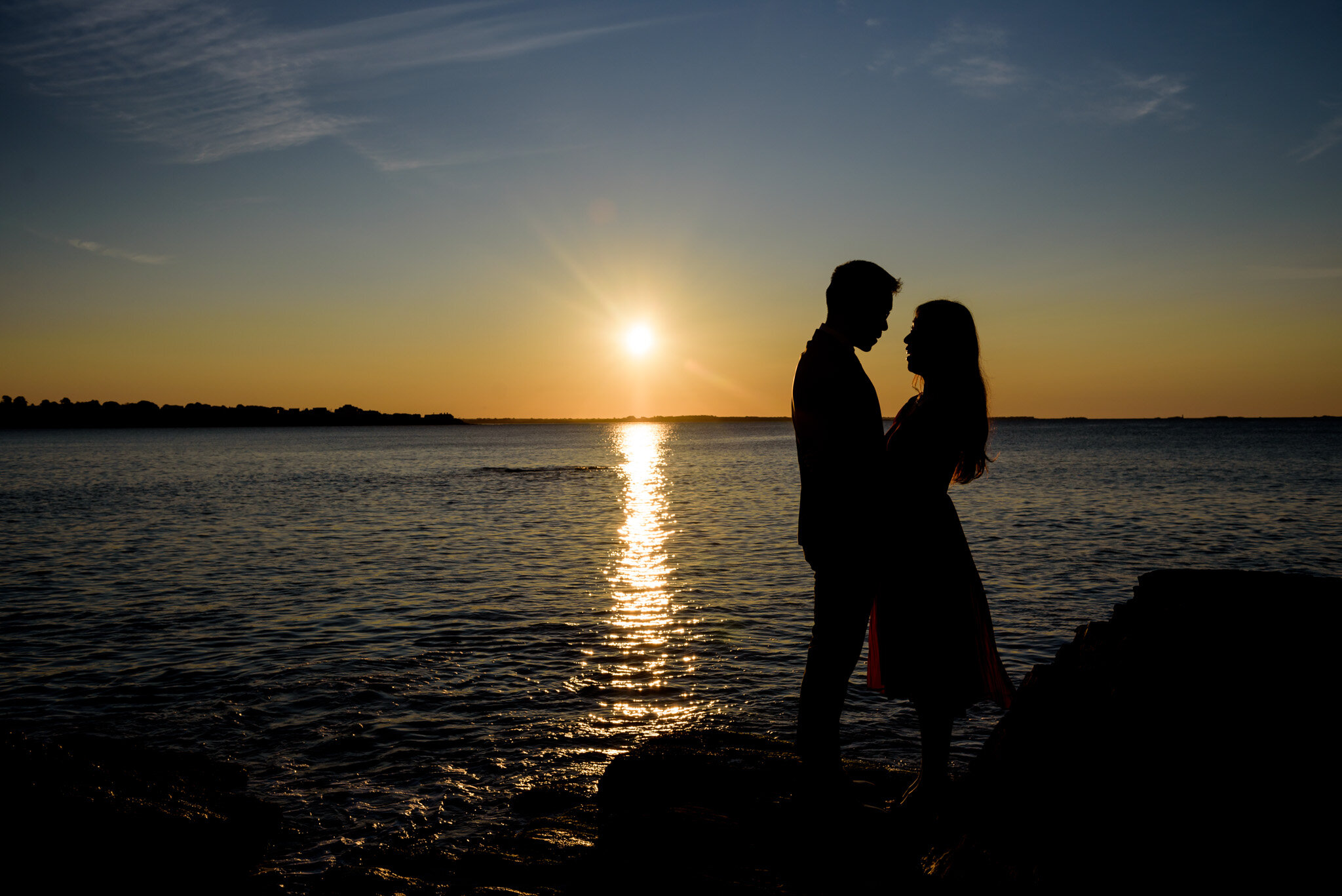 Silhouette of man and woman at sunrise in Newport