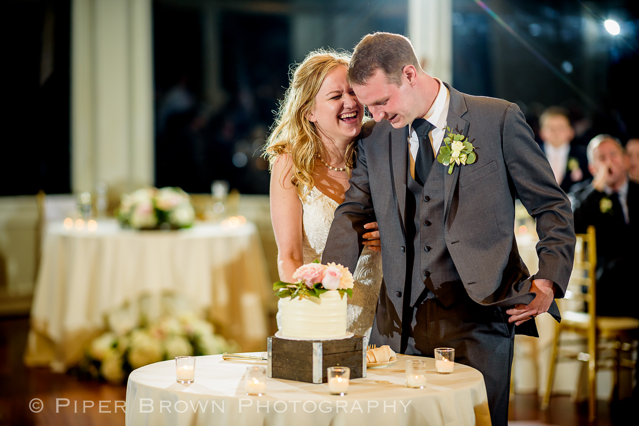 Bride laughing and Groom smiling cutting wedding cake
