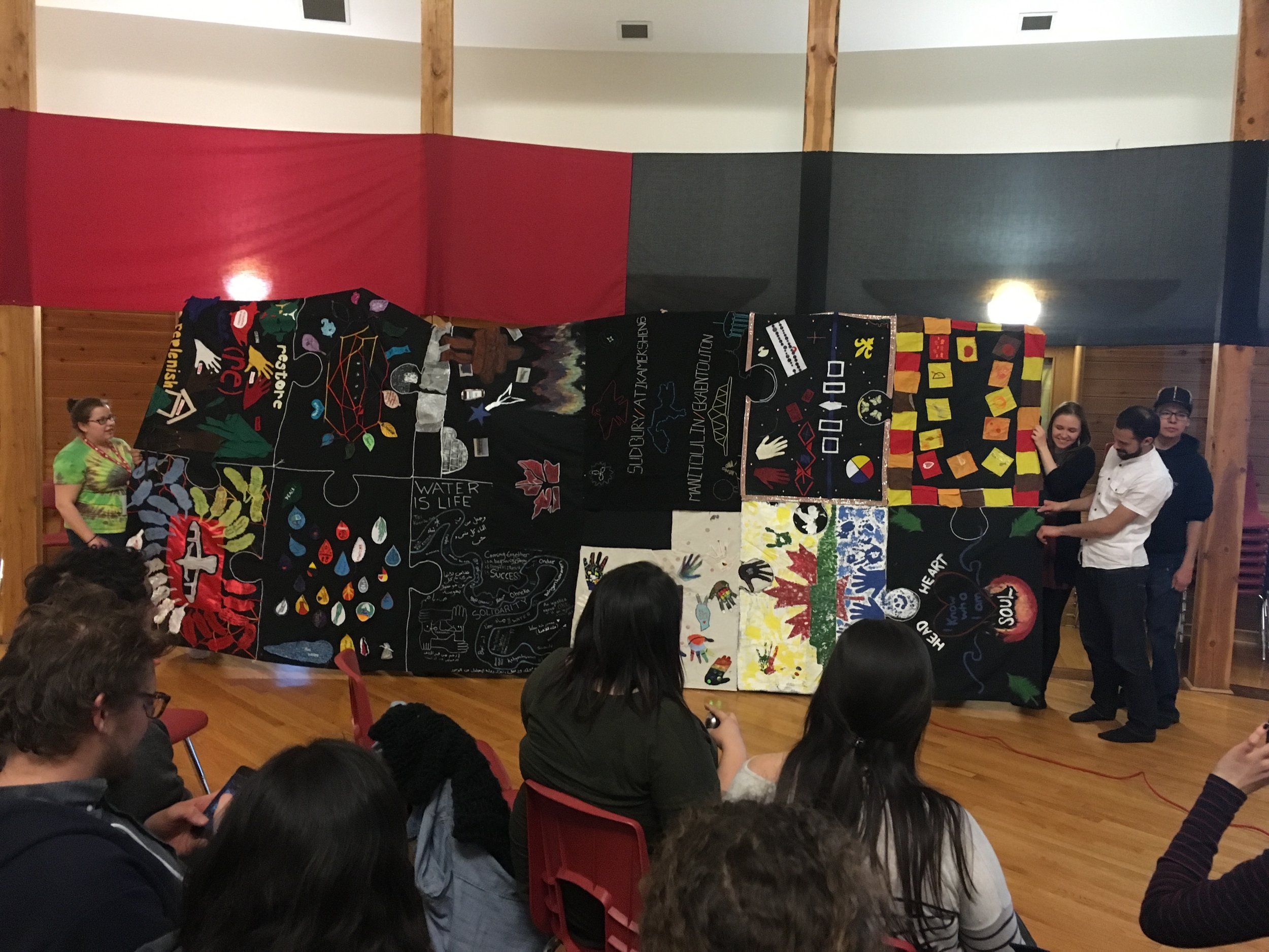 "The ""Story Blanket"" presented at Thunderbird House by the Youth Reconciliation Initiative. Every part of the blanket was completed by a different community, with each patch symbolizing different forms of reconciliation."