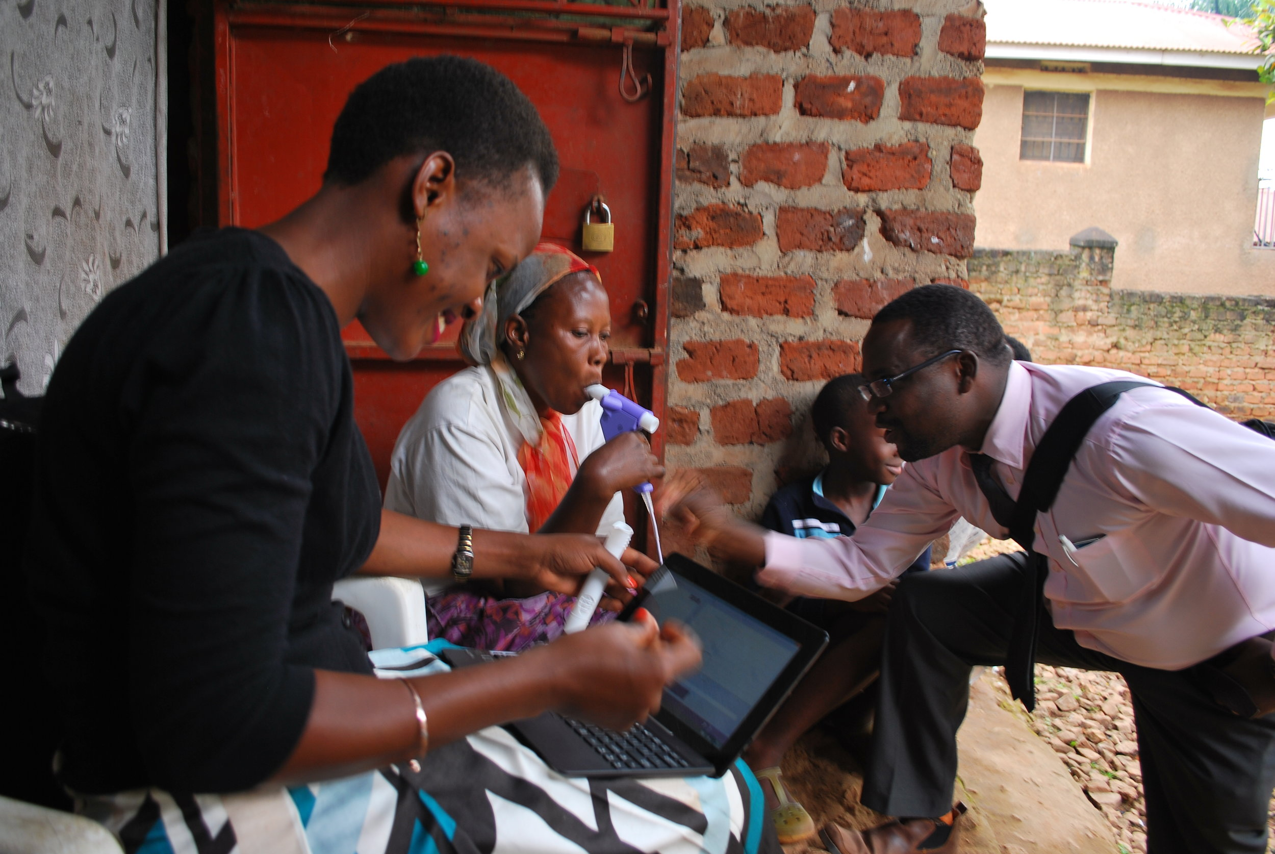 Field worker Faith and Dr. Bruce Kirenga perform spirometry with a study participant in Kampala.