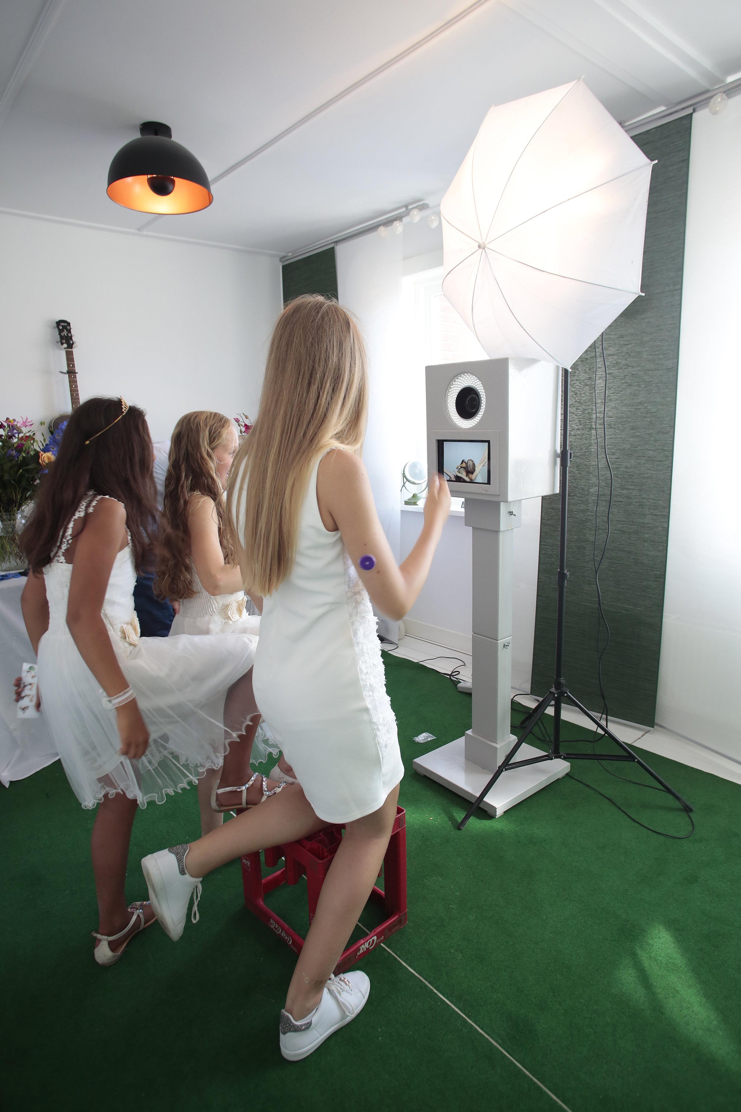 Meisjes op bruiloft op de foto met photobooth.