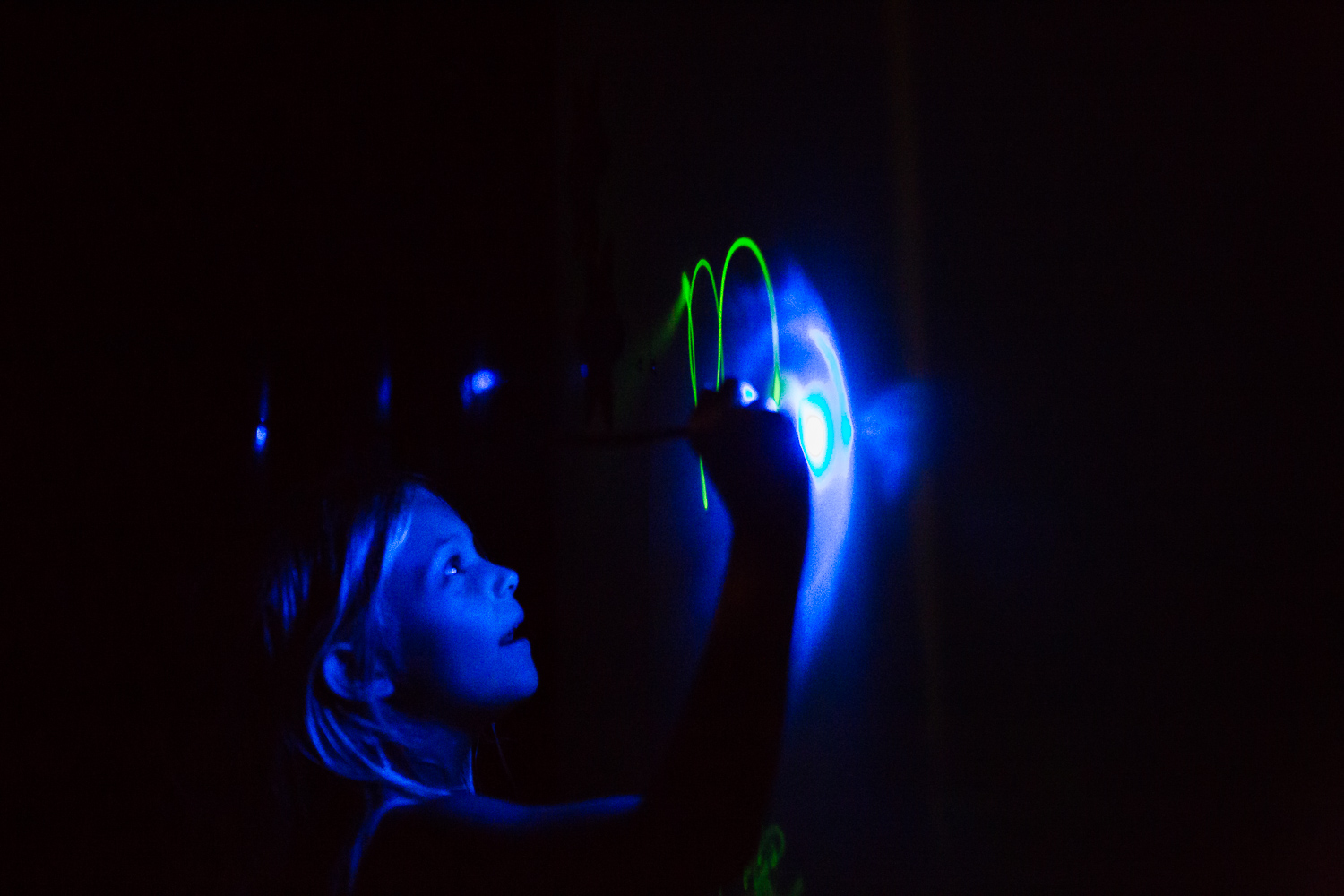 Girl writing on glow in the dark wall