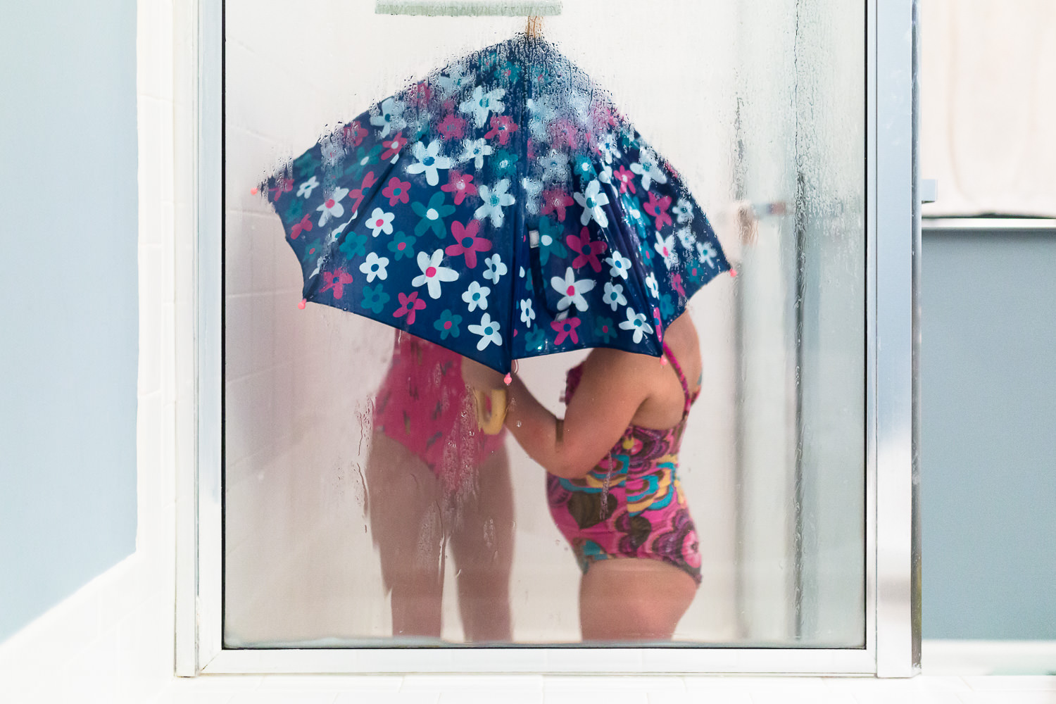 Two kids in shower wearing bathing suits under an umbrella