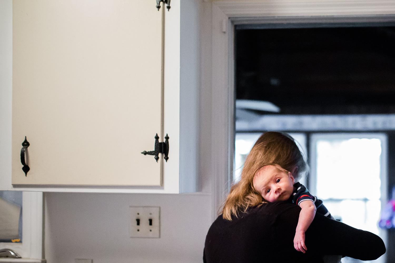 Mother holding newborn on her shoulder