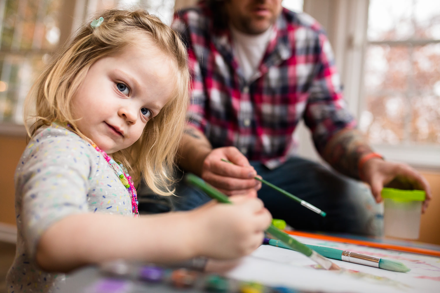 toddler paitning with water colors with her dad
