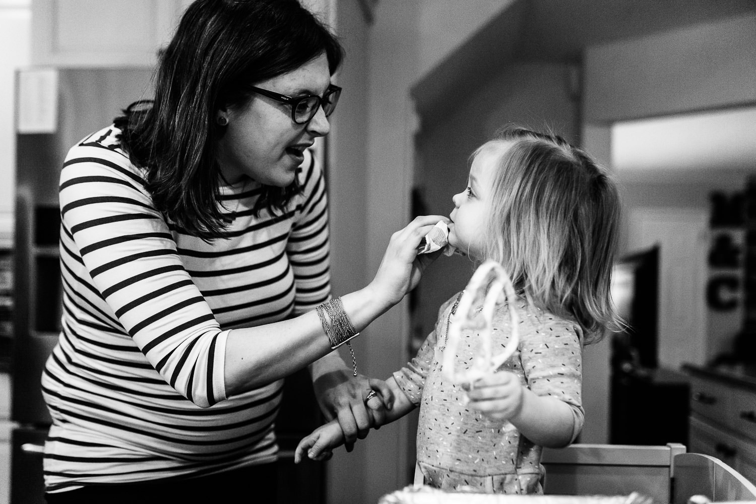 mom wiping cookie dough off of face of little girl
