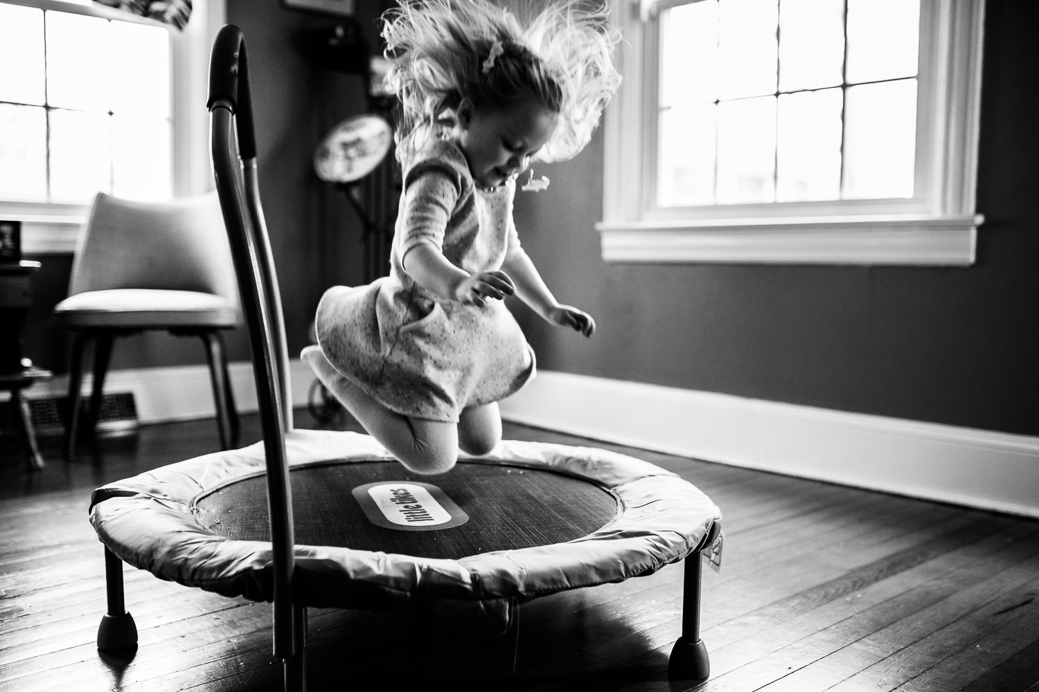 candid photo of little girl jumping on trampoline