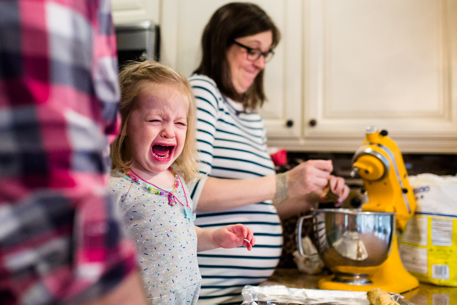 lifestyle photo of little girl crying at kitchen counter