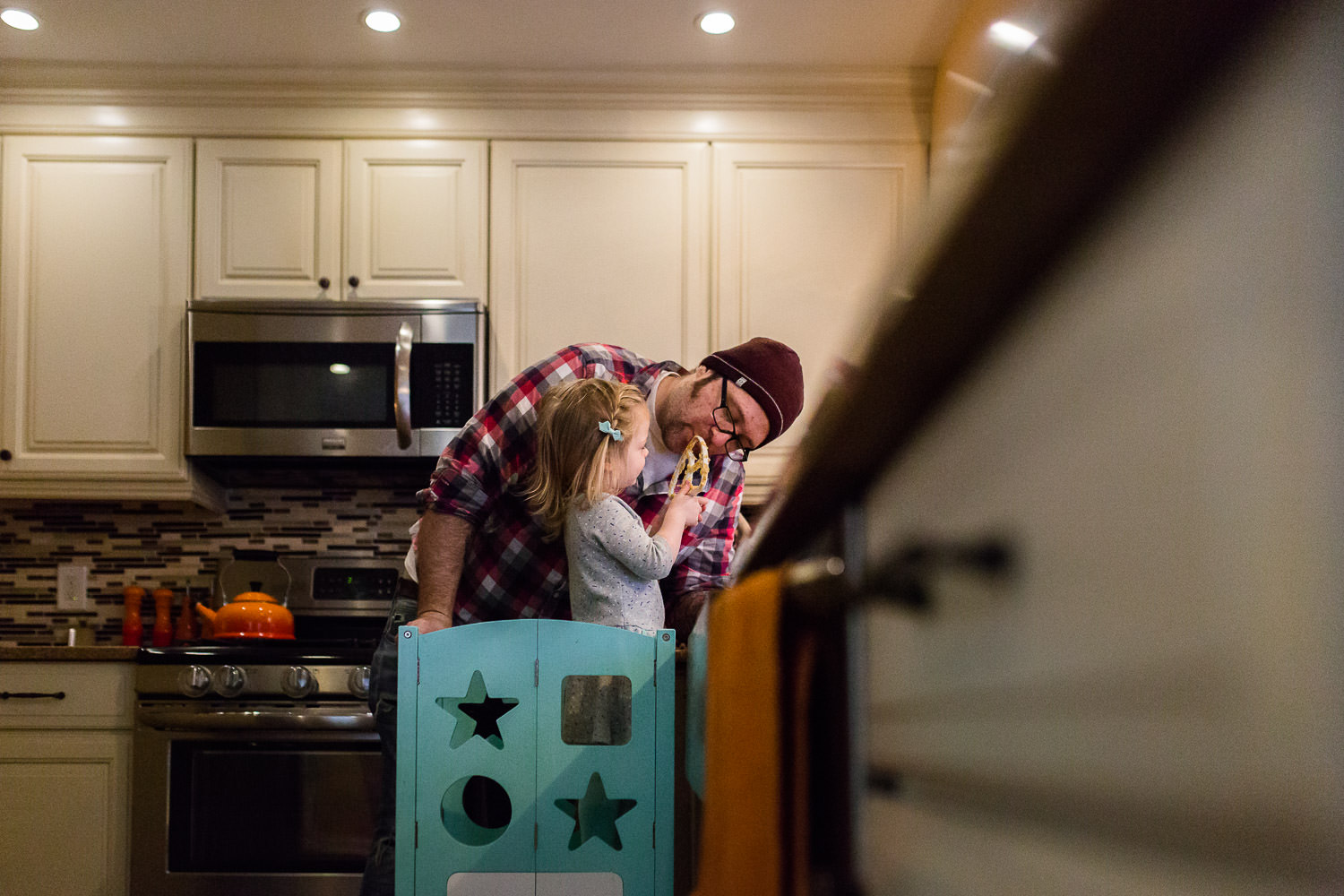 toddler girl sharing cookie dough with dad in kitchen