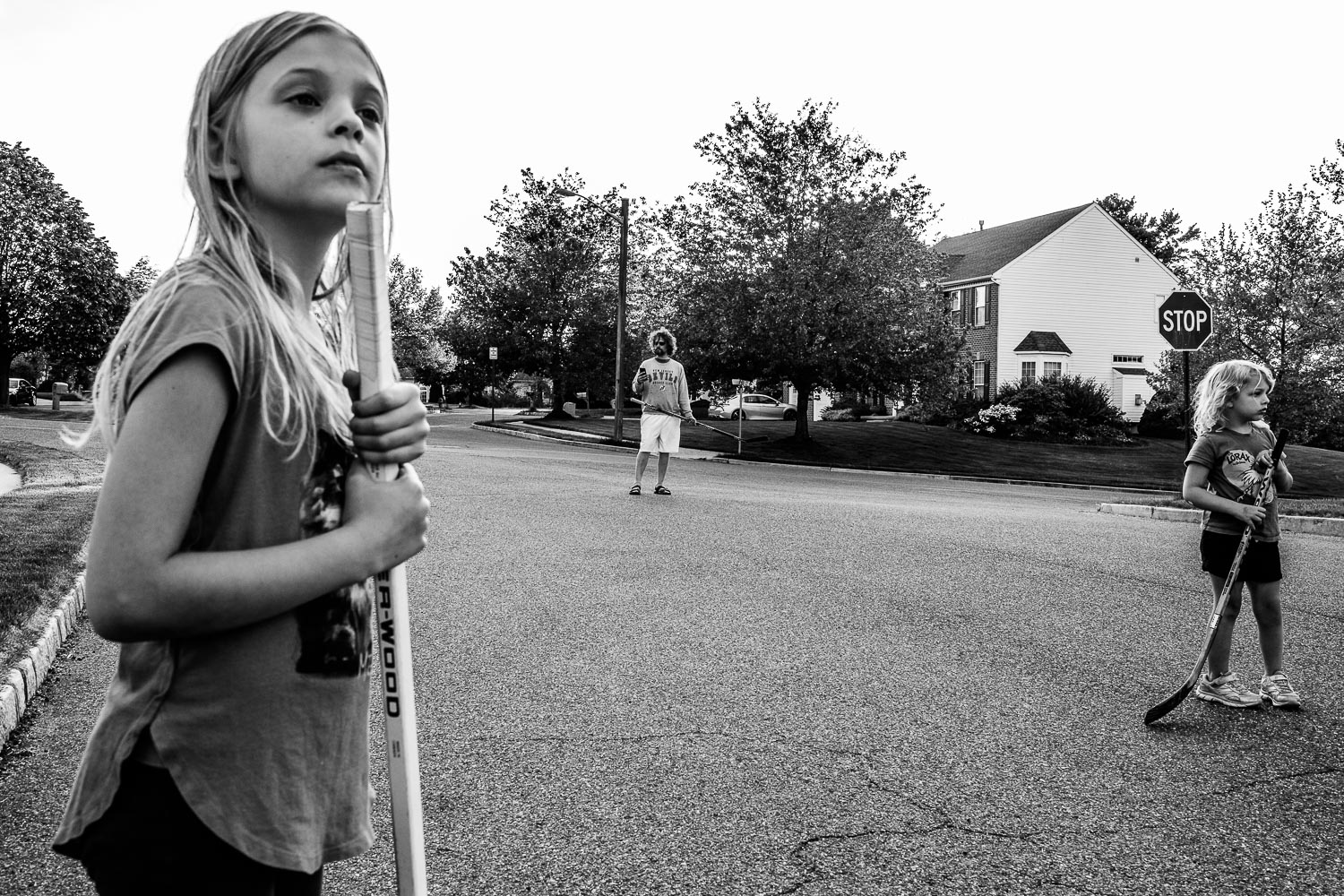 Two girls and dad in street with hockey sticks