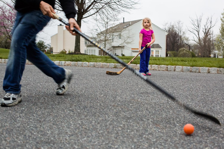 little girl playing street hockey