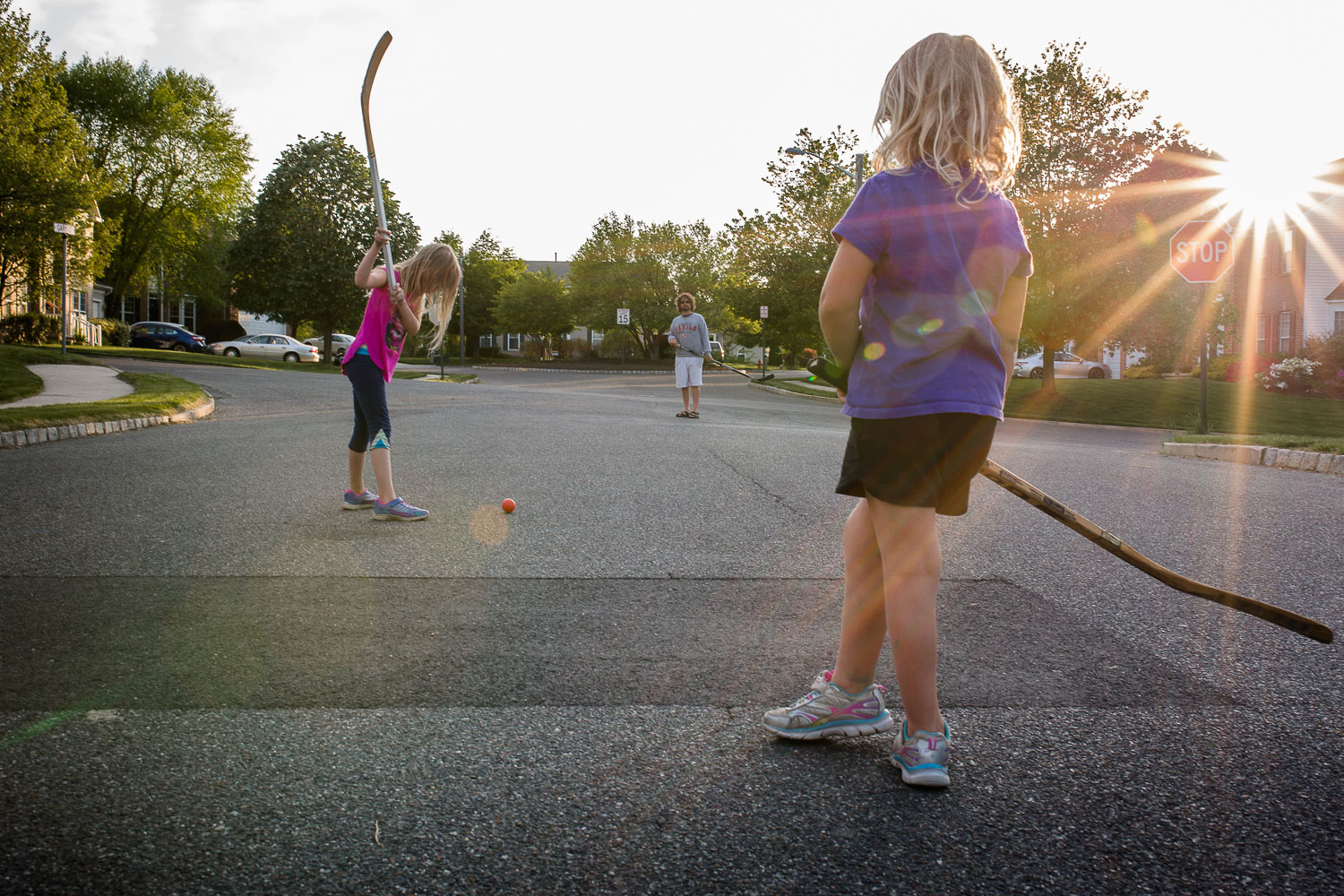 two girls and father playing street hockey with sun flare