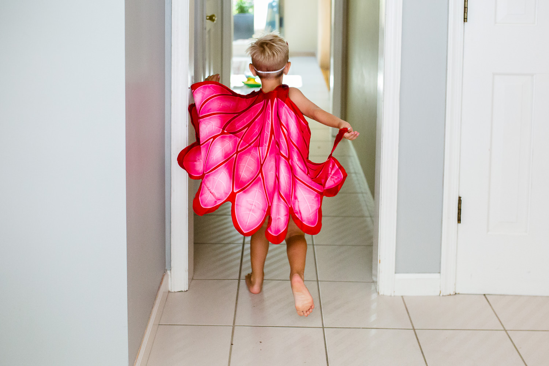 little boy running in red cape