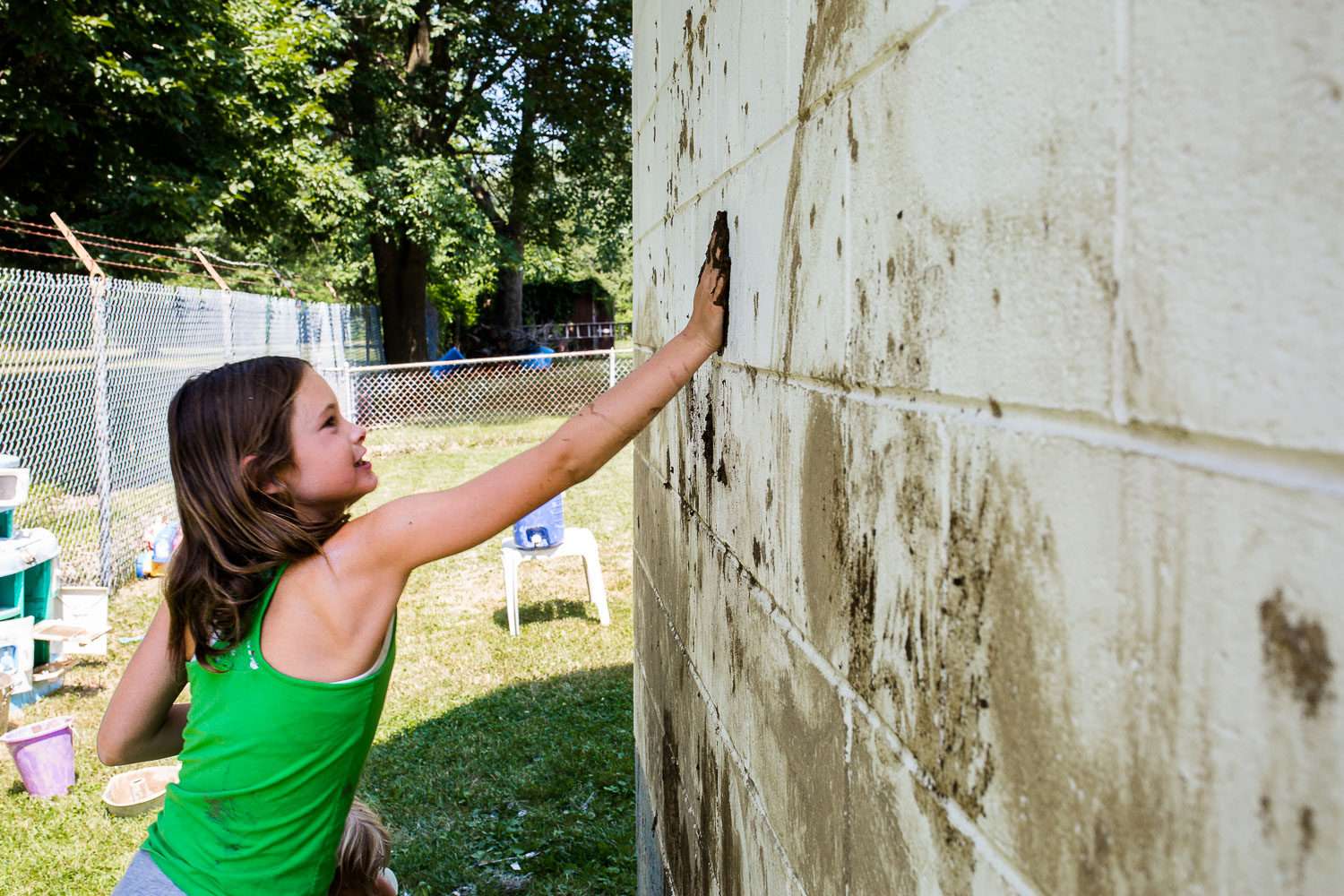 Girl making mud handprint on garage wall in backyard.