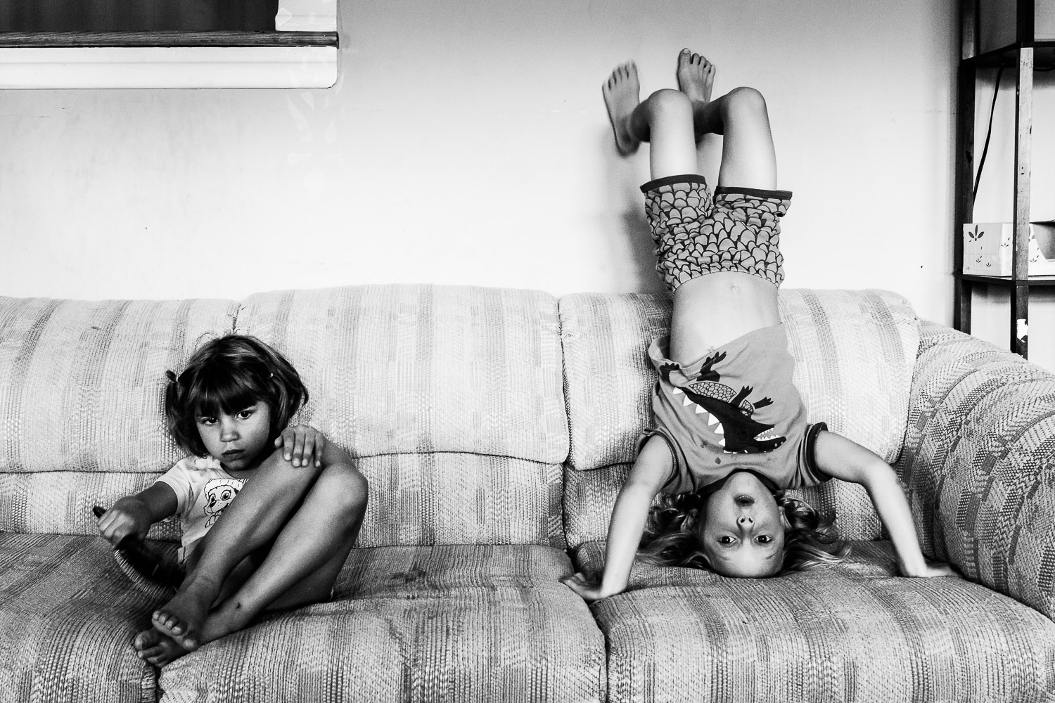 Black and white photo of little girl and boy standing on his head on couch.