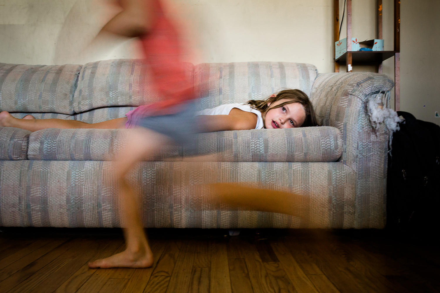 Boy in blur of motion running past sister laying on couch.