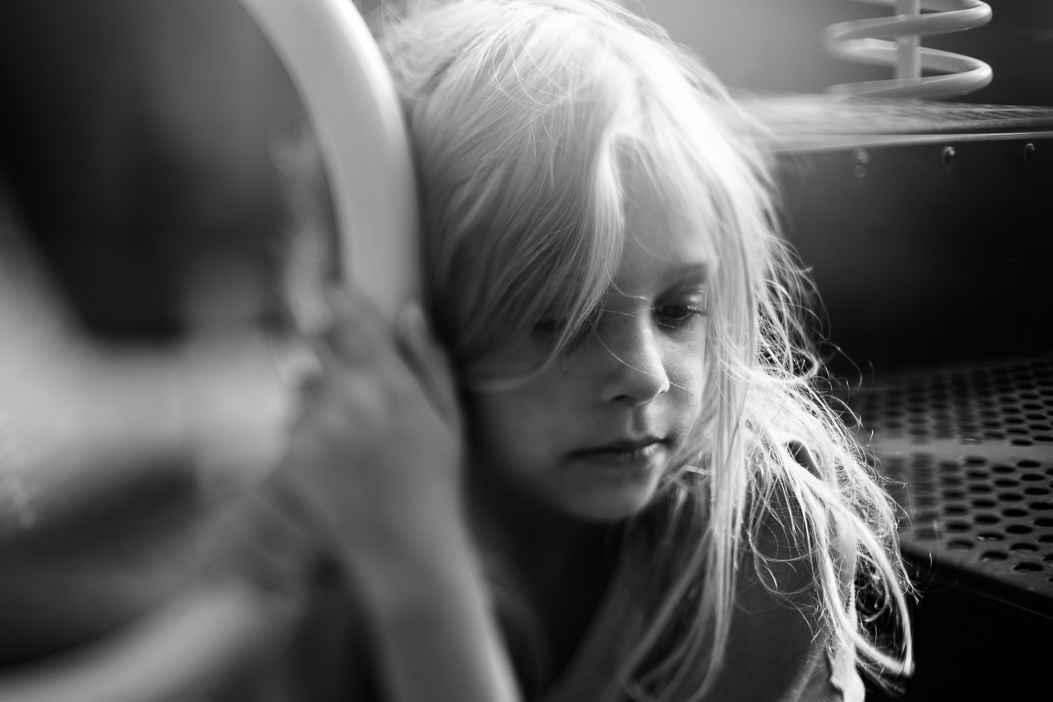 black and white artistic photo of girl on playground looking melancholy