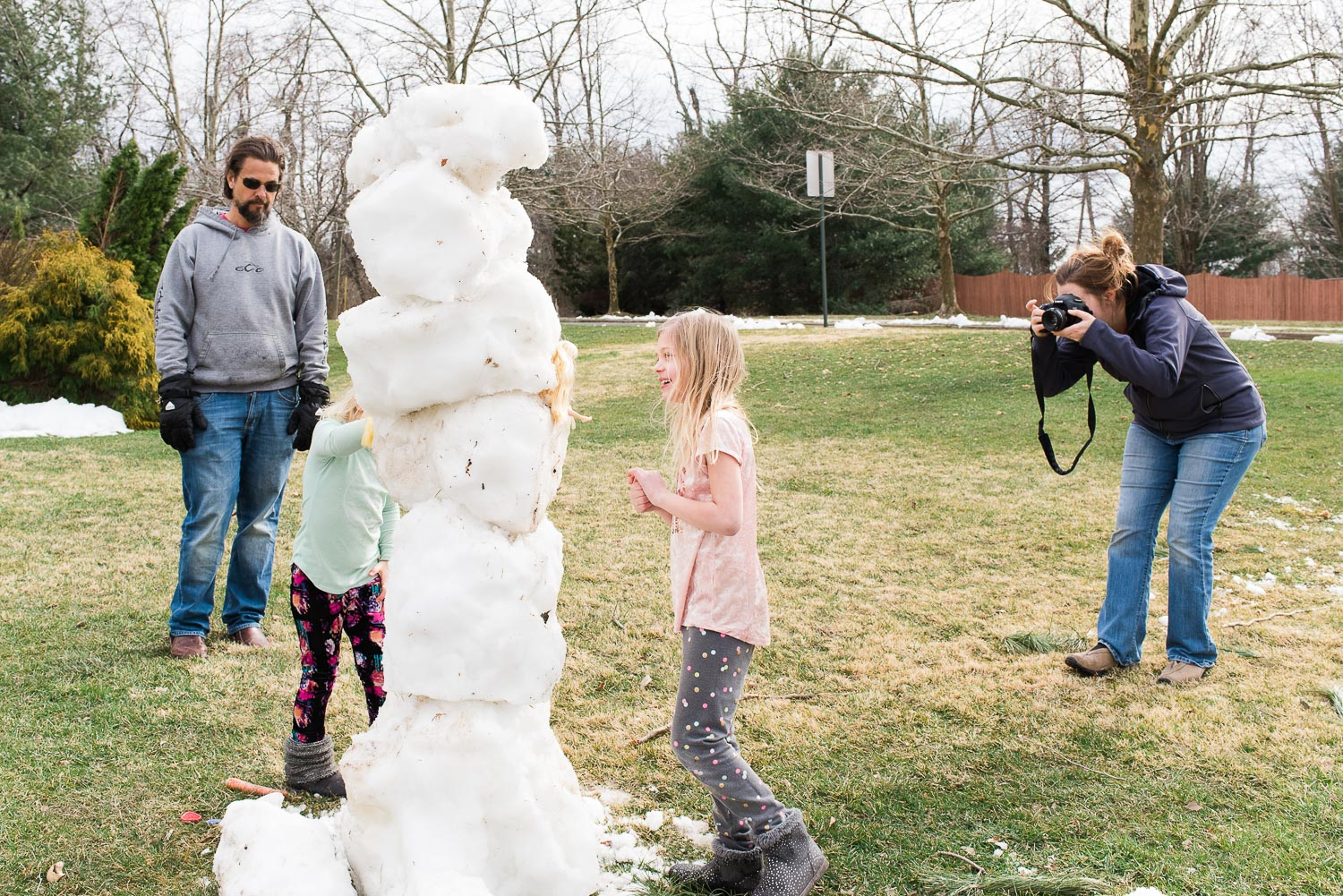 mother photographing kids and father building a snowman