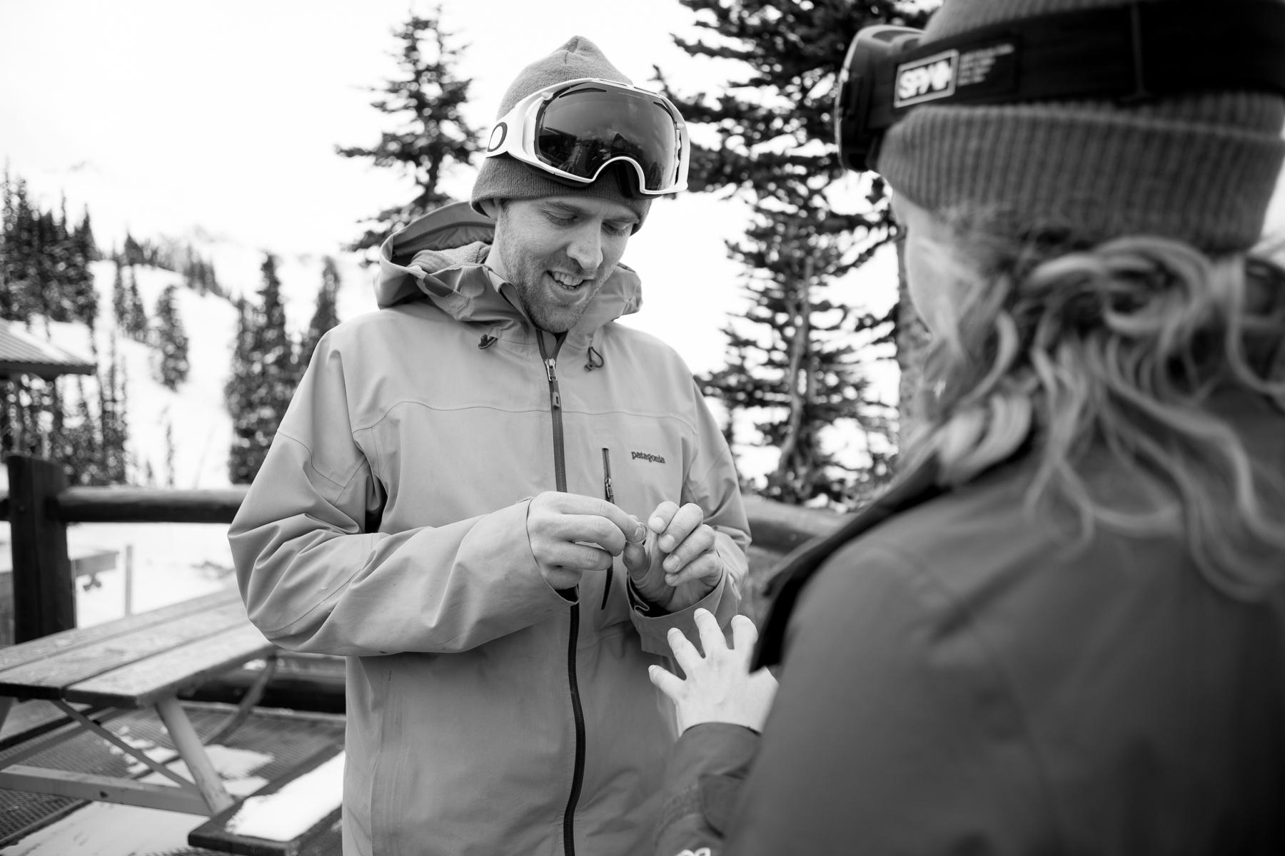 groom putting ring on bride finger on ski resort