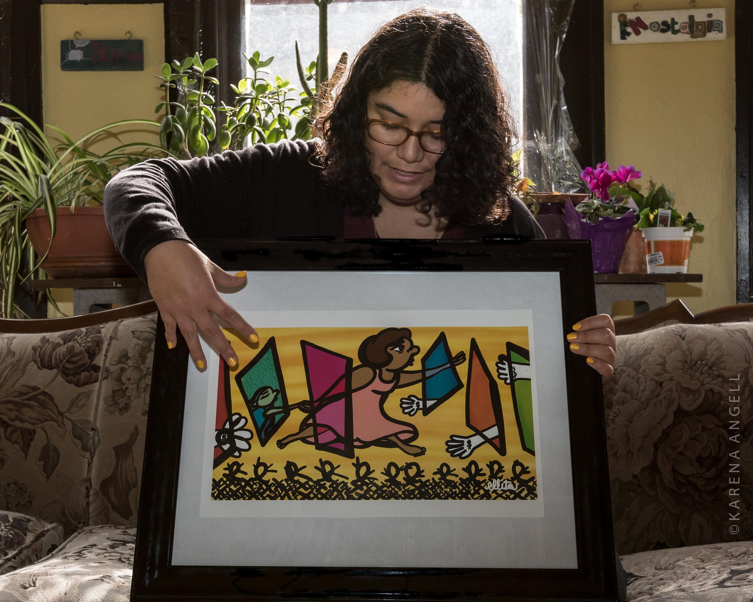 "Ella Mendoza holds her artwork, ""Cruzando Fronteras"" or ""Border Crossing"". (Photo by Karena Angell)"