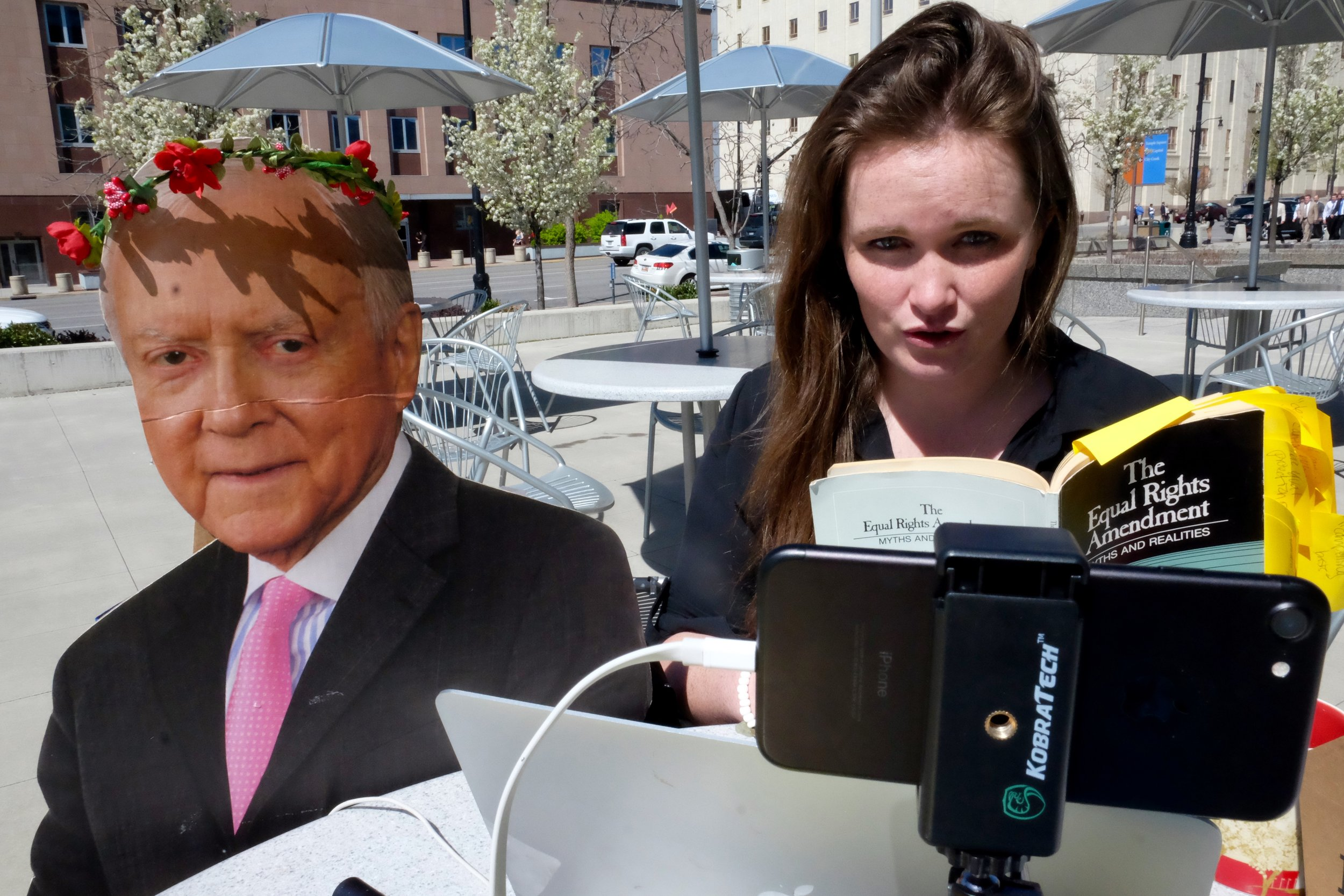 Madalena McNeil with a cardboard cutout of Senator Orrin Hatch in front of the Wallace F. Bennett federal building in Salt Lake City. (April 1, 2017) Photo by Andrea Smardon