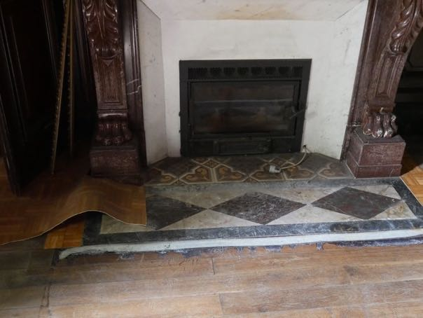 linoleum pulled off to expose beautiful wooden floors and marble hearth.