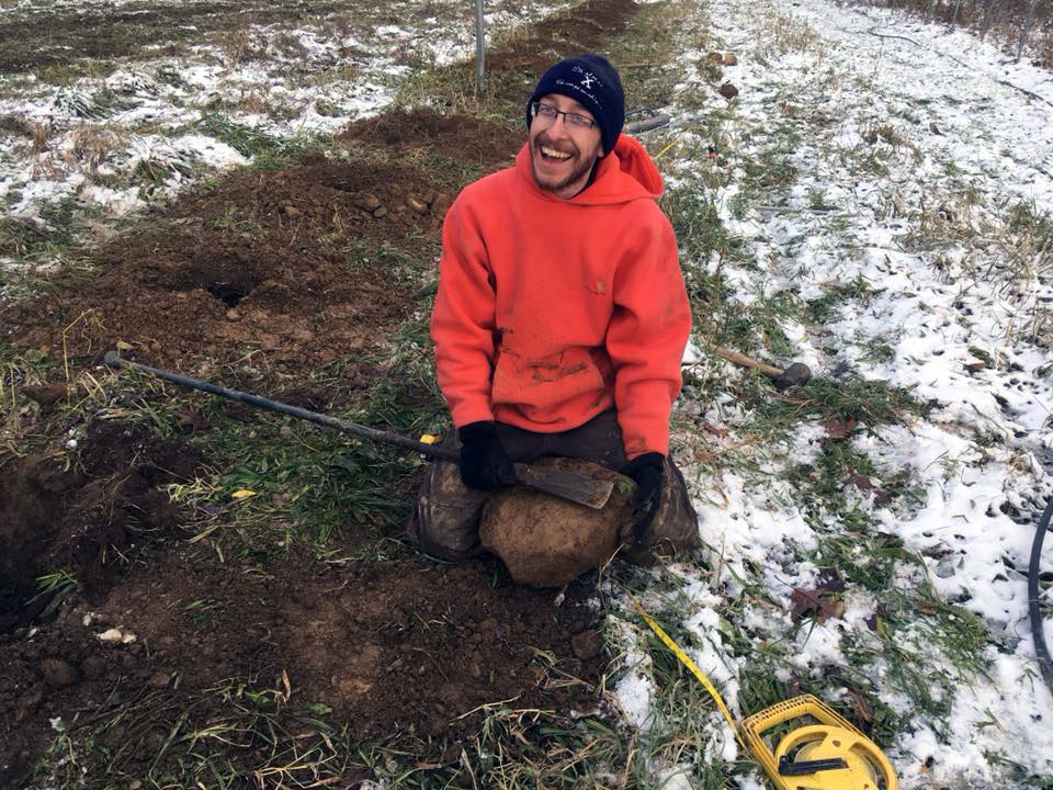 Jason with one of many big, stupid rocks we dug out of the earth before setting the high tunnel poles.