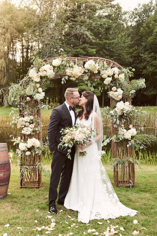 Bride and groom kiss in front of ceremony arch at DeMaranville Farm in Saratoga Springs, NY