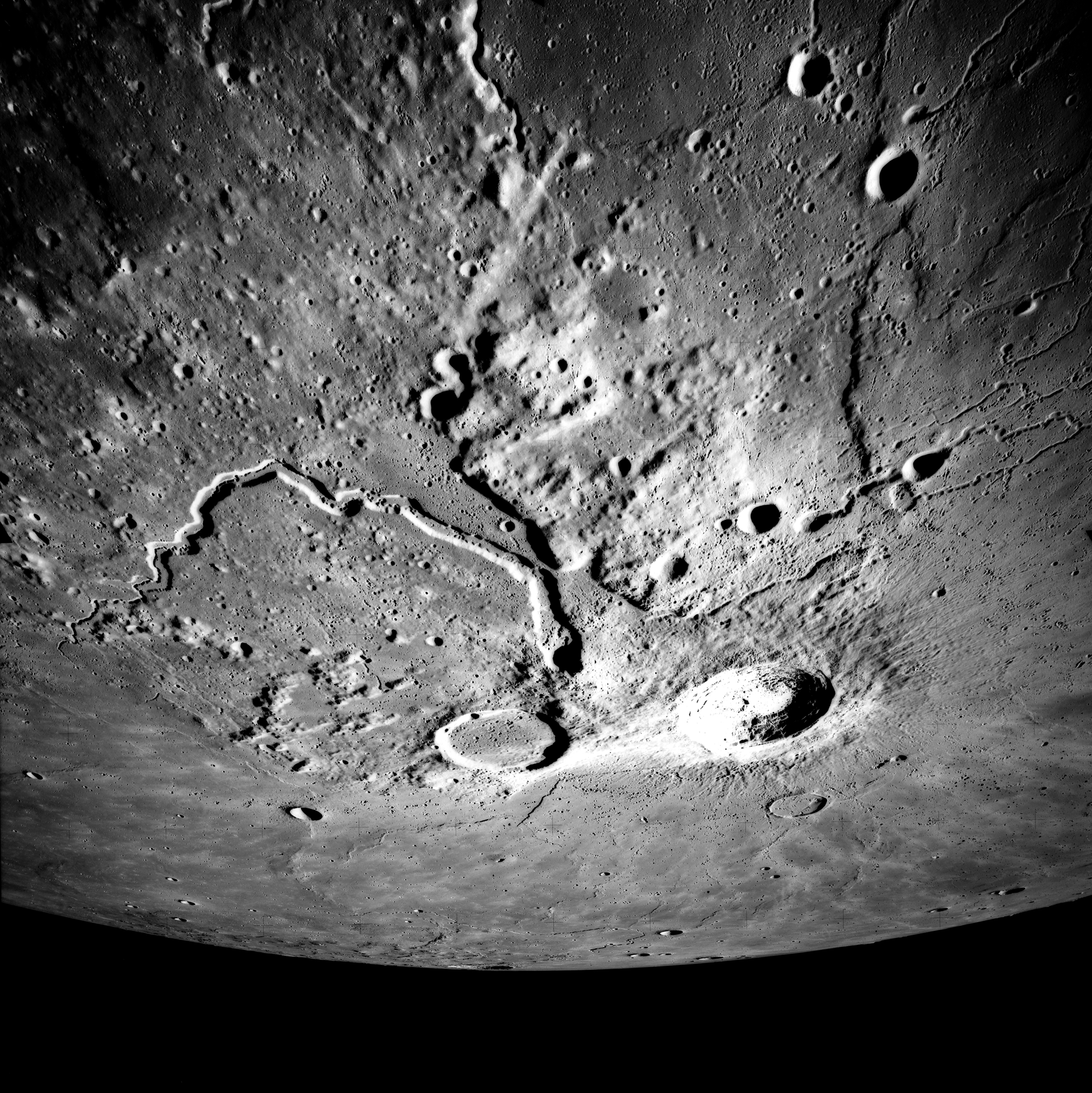 (Left) Apollo 15 Mapping Camera image (A15-M-2610) of the Aristarchus plateau. Note the large, fresh Aristarchus crater, as well as the sinuous rille Vallis Schroteri. The entire uplifted, hummocky plateau has been mantled by pyroclastic materials.  (Right) Topography of the Cobra Head region of the plateau.All of the major volcanic features on the plateau (Cobra Head, Vallis Schroteri, the pyroclastic deposit, and the irregular cones) may have been formed from an eruptive vent located at Cobra Head.