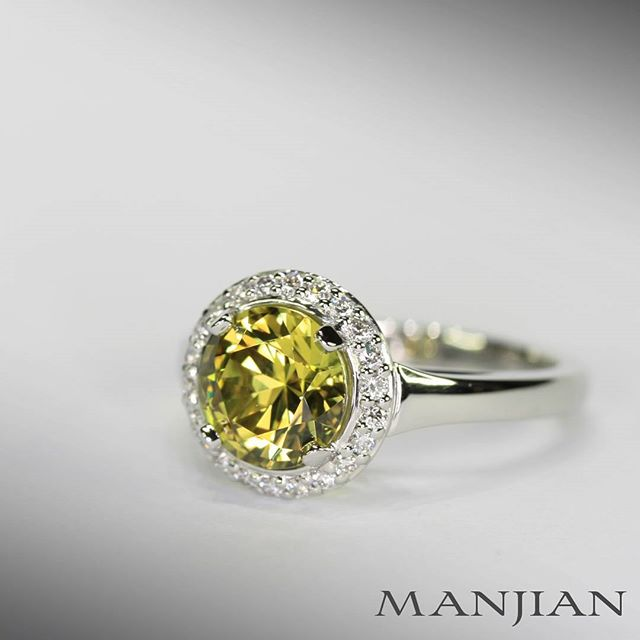 An Australian untreated natural yellow sapphire, cut in Queensland to the proportions of a triple excellent graded round brilliant cut diamond and set in a custom made ring in platinum with a diamond halo border.