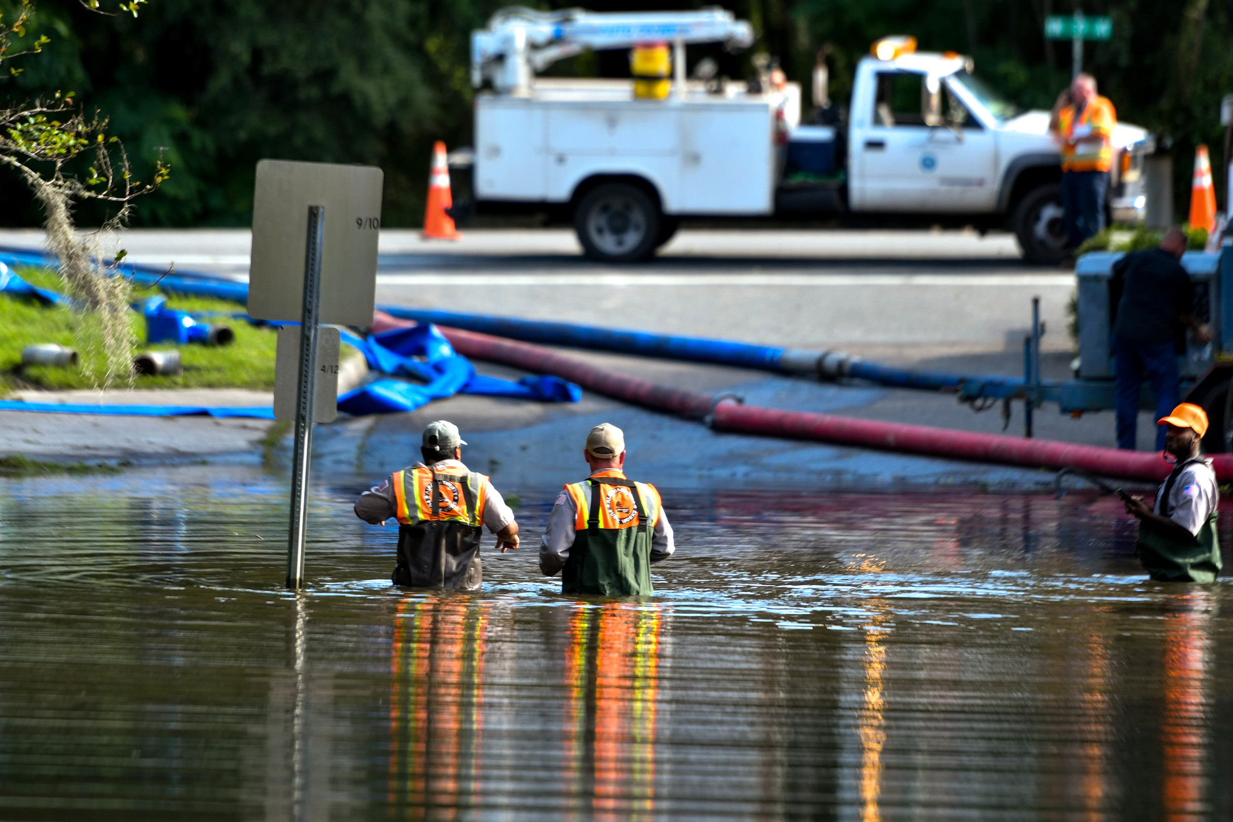 Workers walk out of the excess stormwater at the entrance of the Robin Lane Neighborhood. It took more than two days to make the road accessible. (Grace King / WUFT News)