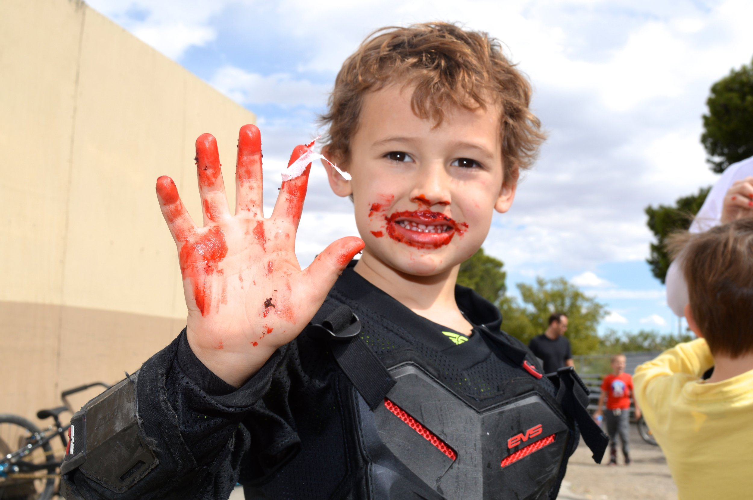 Holding up his age in fingers, a full-hand now! Covered in red cupcake icing, of course.