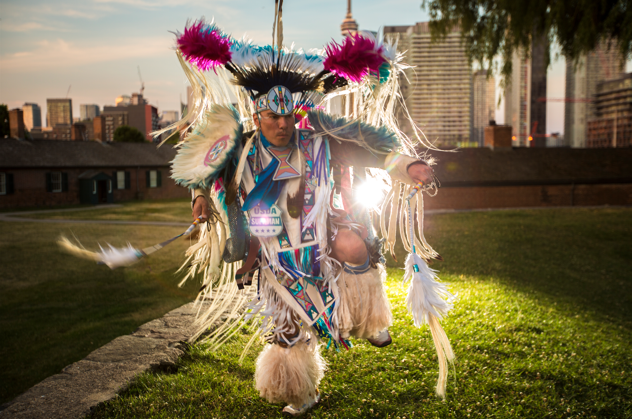 SUPAMAN in traditional Native American fancy dress, crafted by his matriarchs, dancing in the natural, vibrant light of Mother Nature juxtaposed by the metropolis backdrop of our concrete&steel, cold&engineered current culture; a metaphor of who is SUPAMAN, riding the rails of cyber promotion injecting our world with a positive, artistic, spiritual existence;  a neon lit, electrified, fancy-dancing,   rapping Healer.