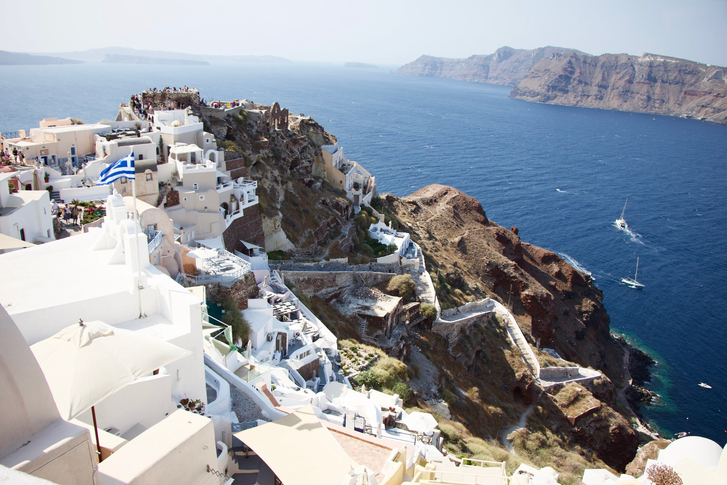 Santorini's iconic white buildings sitting on a hilltop above the deep blue ocean.