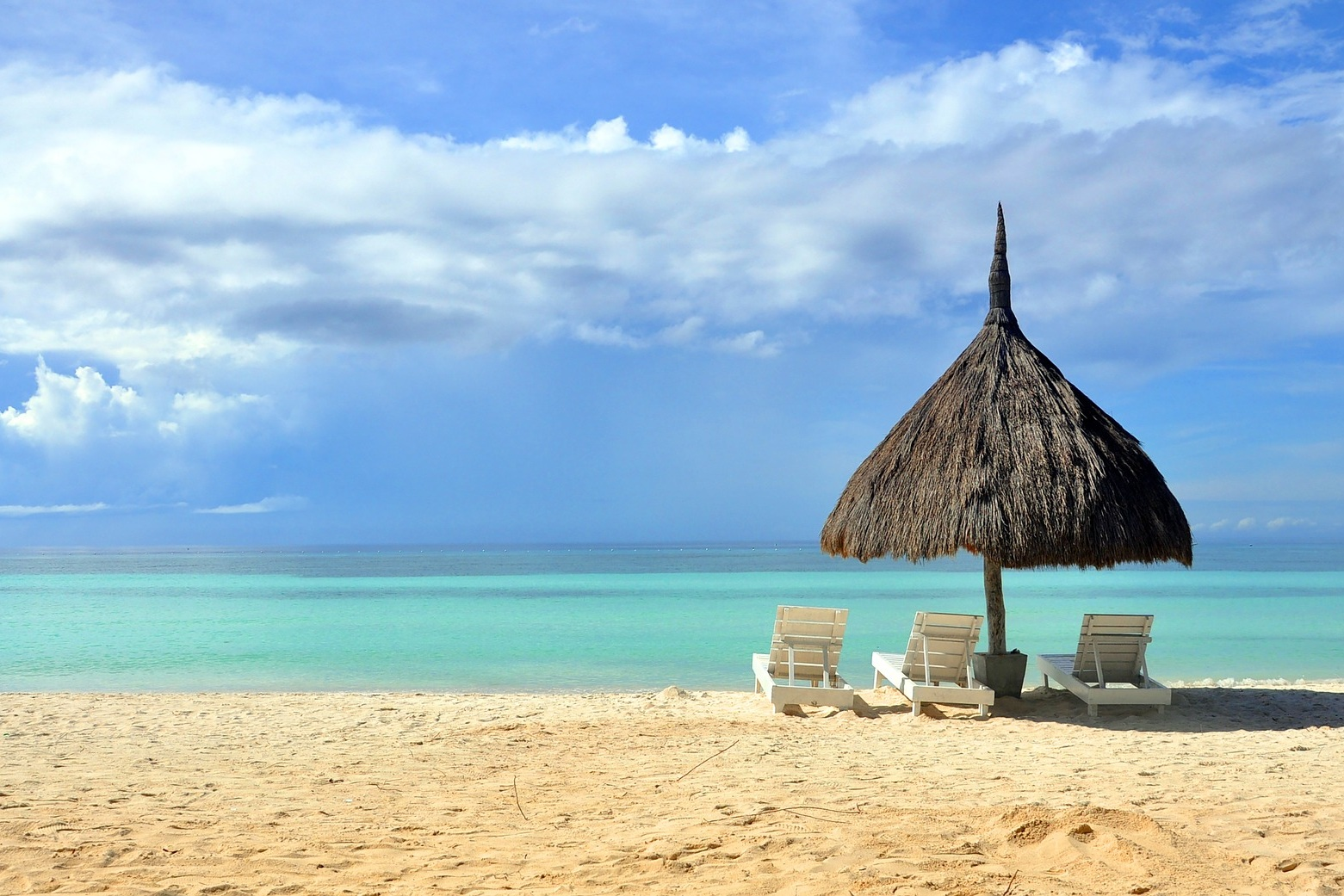A grass hut and lounge chairs sitting on a blissfully empty beach in front of the brilliant blue water.