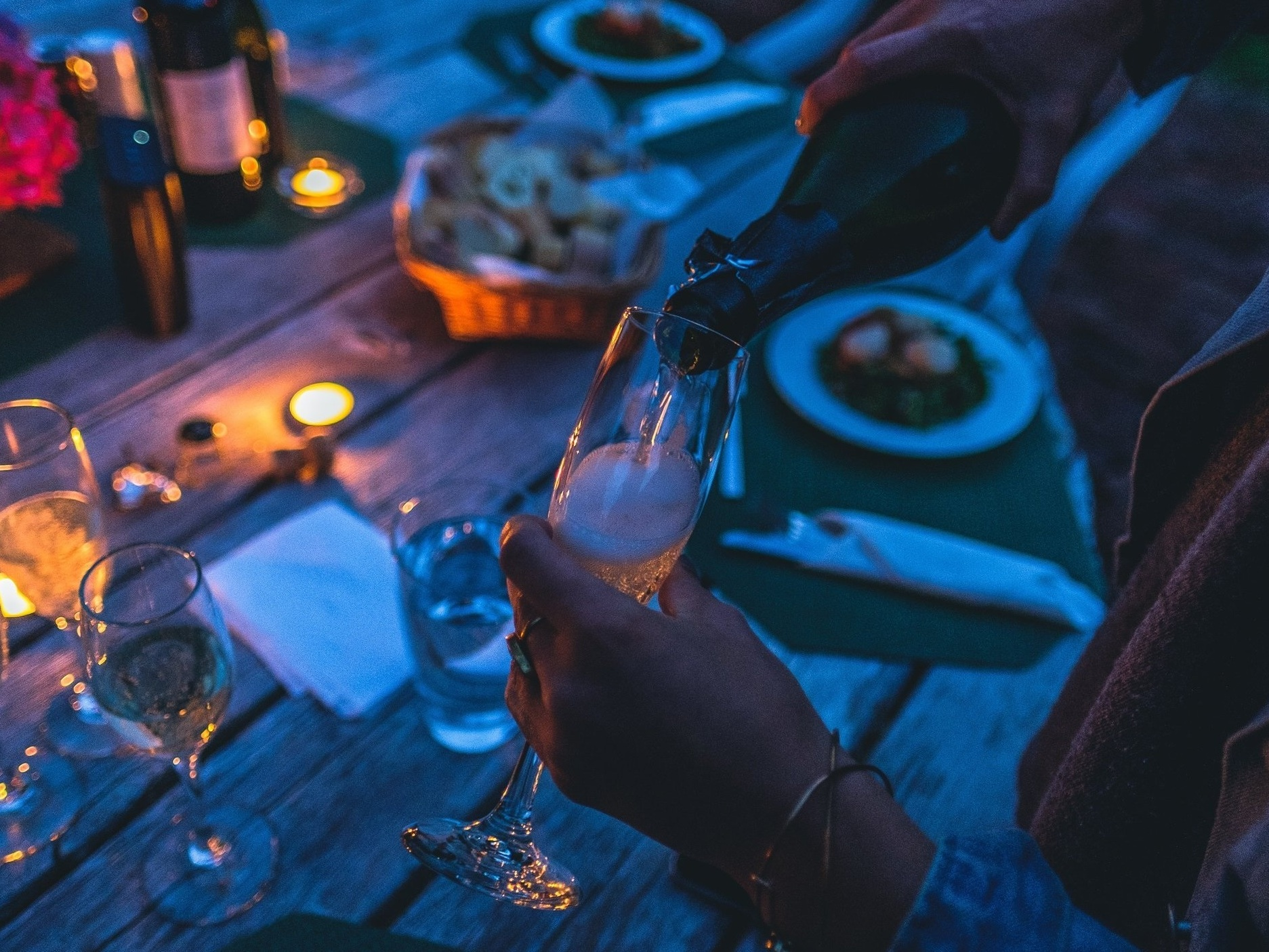 A woman pours wine above a rustic table laid with candles, flowers, and dishes.